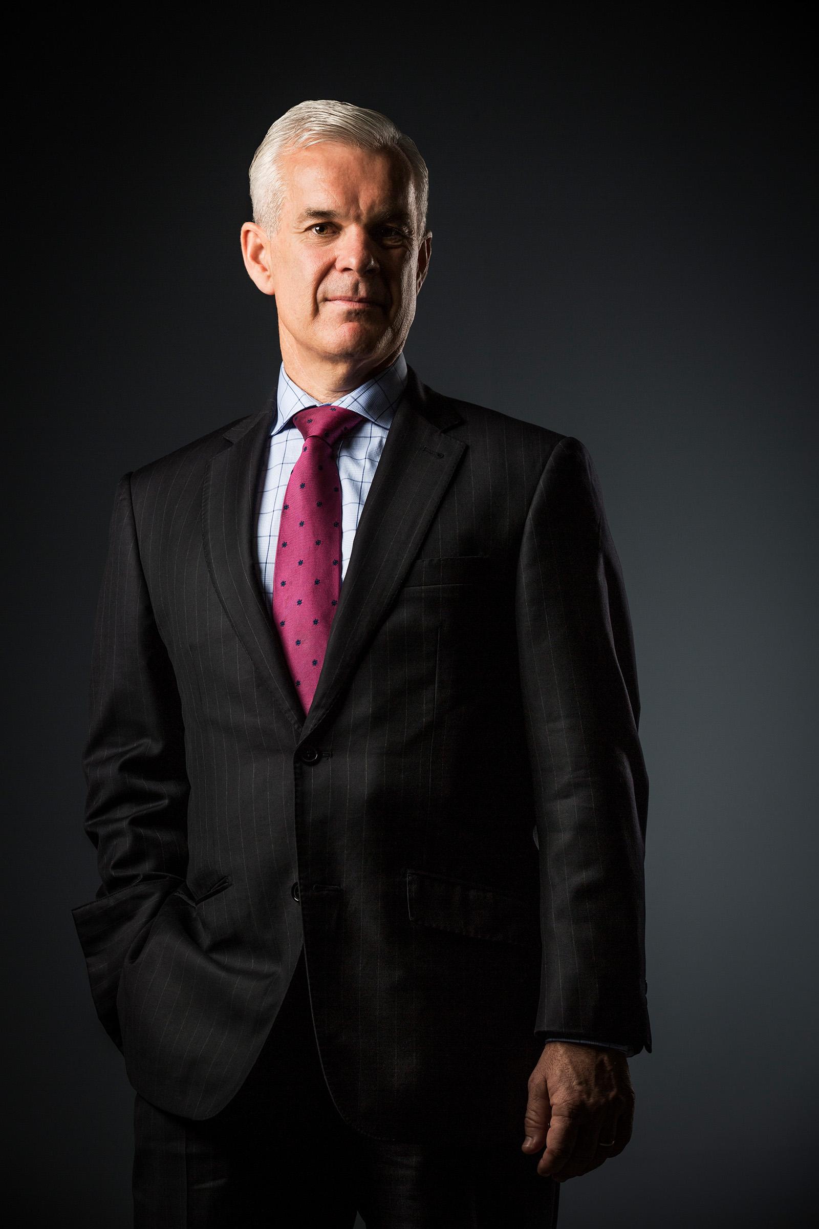 Corporate studio portrait David Hosking Allianz grey graduated background hand in pocket wearing business suit