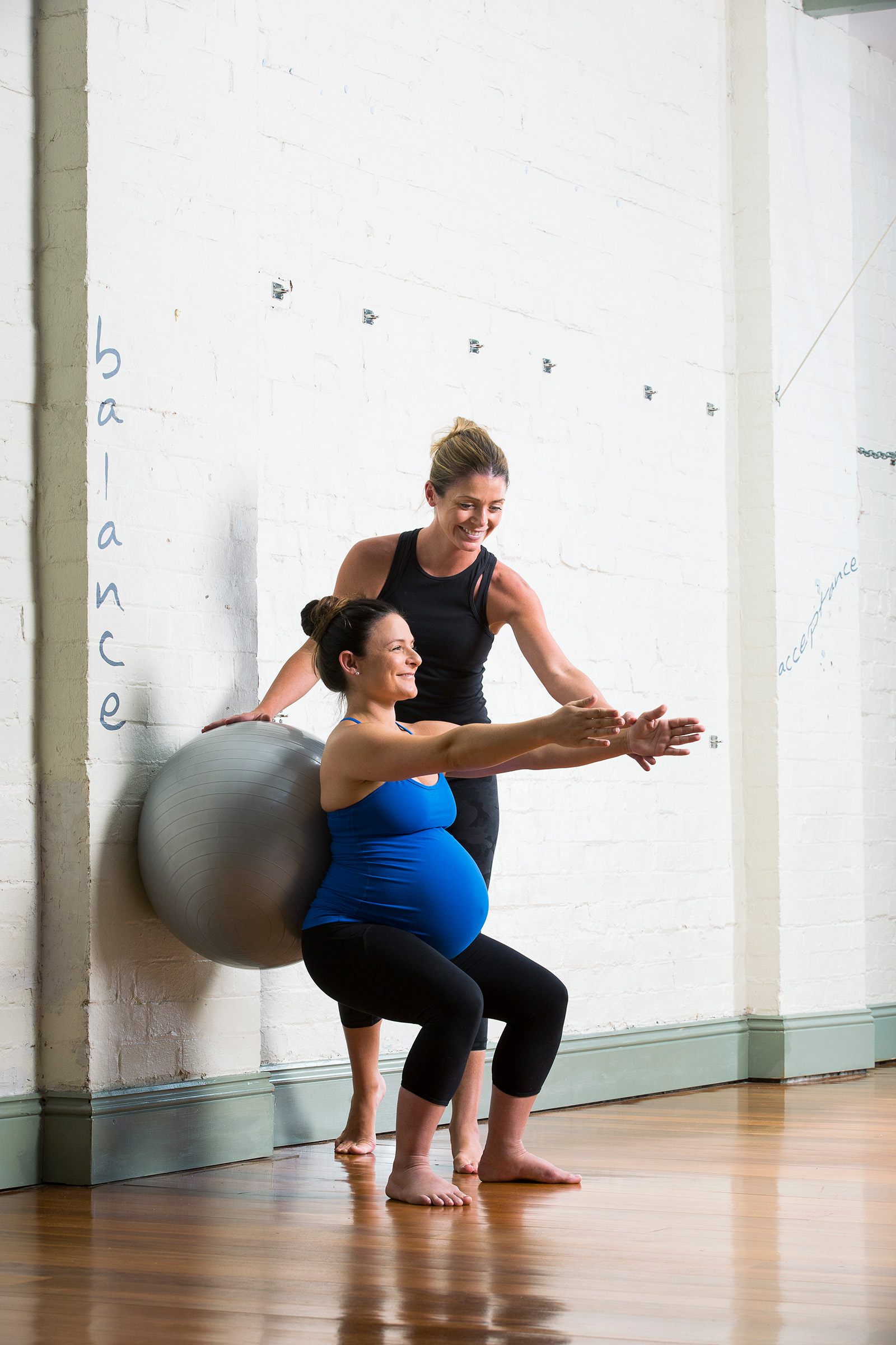 Editorial location fitness photography for Fitness Australia of pregnant woman squatting and being instructed by trainer