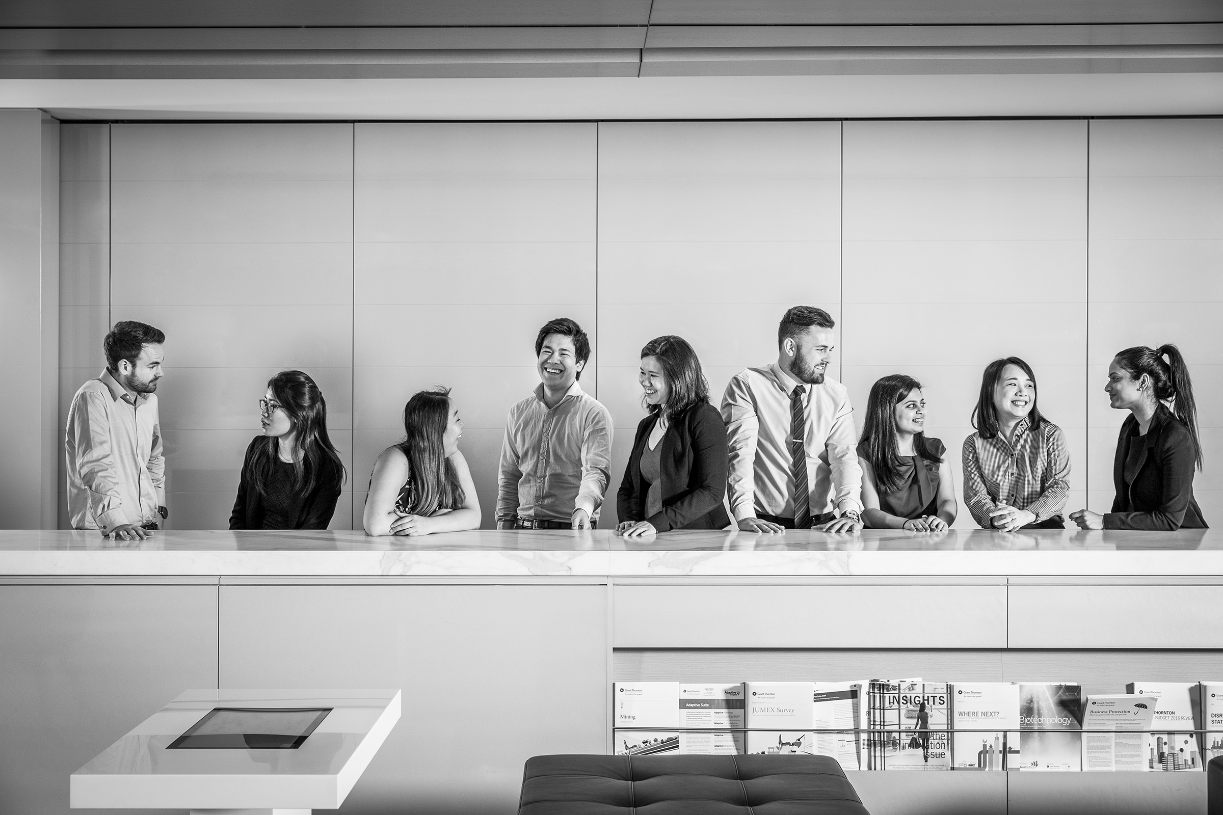 Corporate environmental casual group photography Grant Thornton graduates along a bench office background
