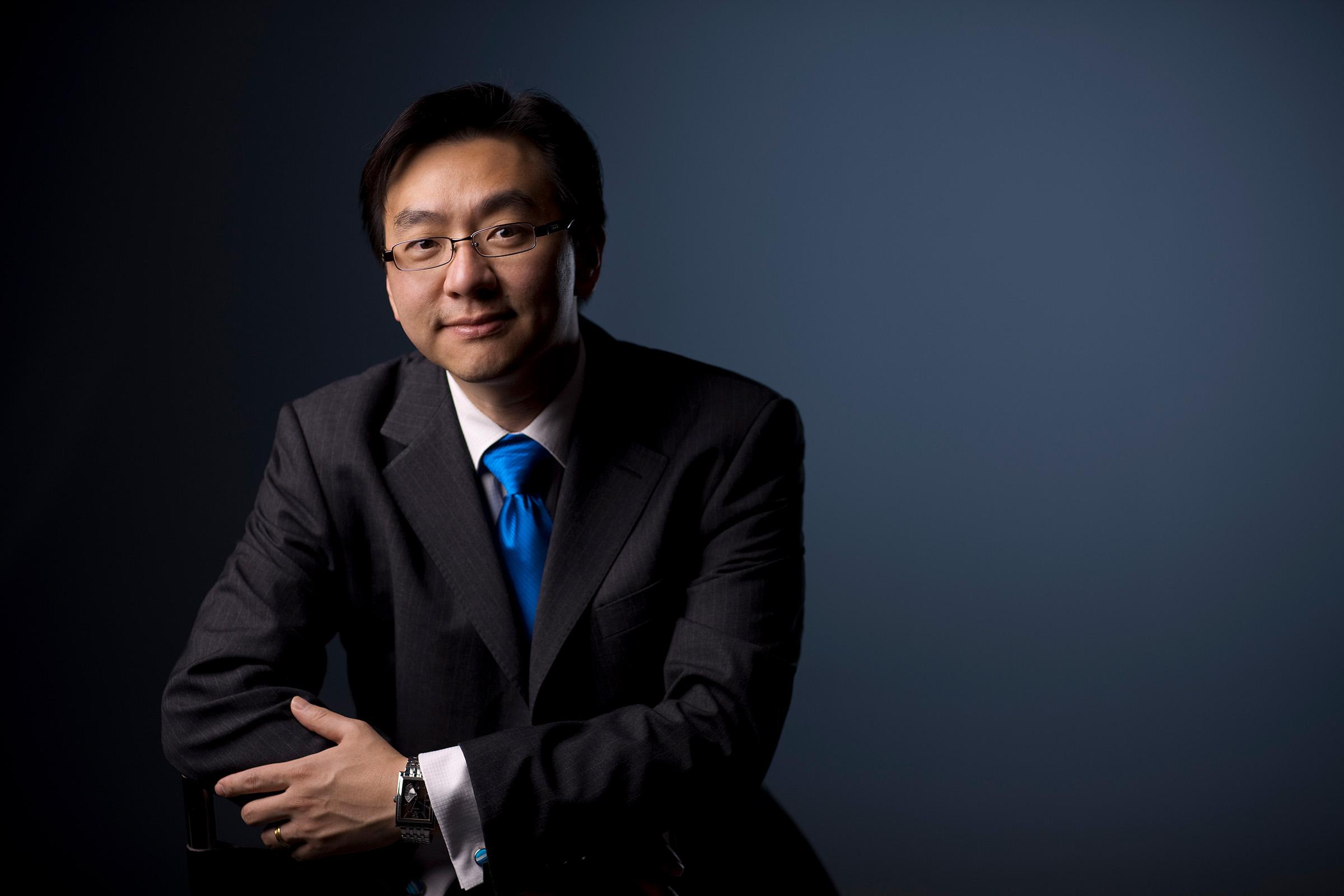 Corporate studio portrait photography IIA male glasses blue grey graduated background