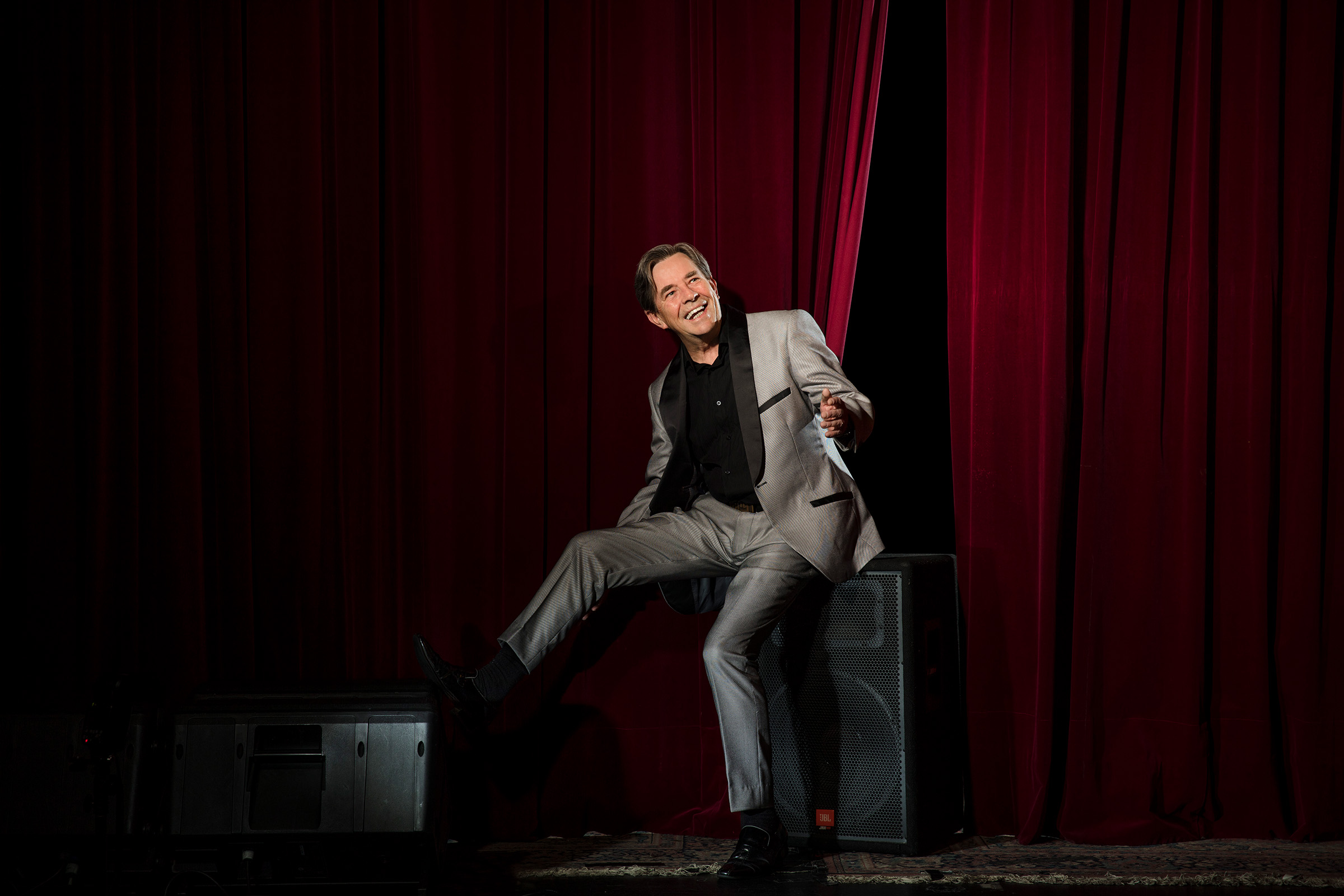 Editorial location photography of Australian singer John Paul Young love is in the air on stage grey black suit