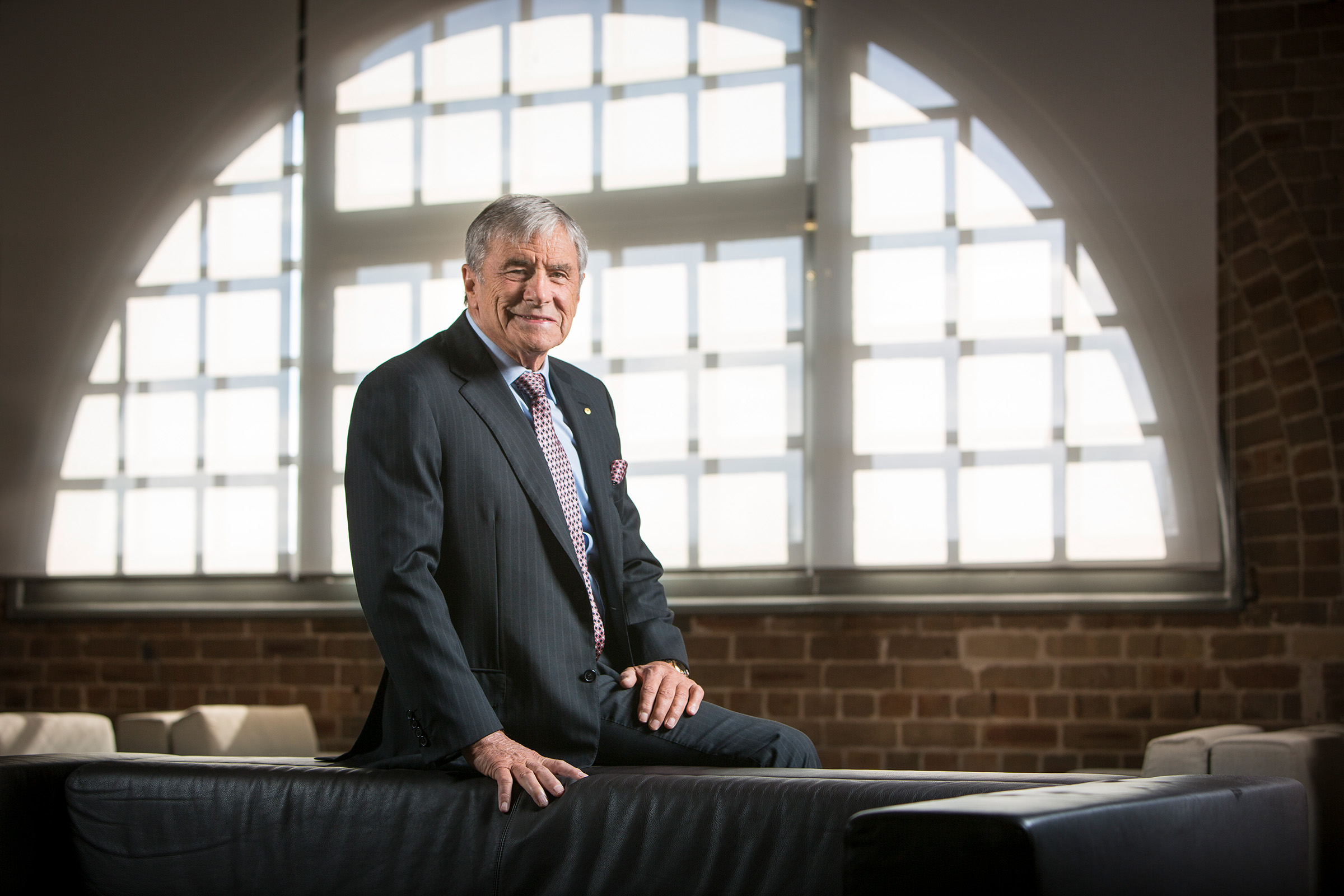 Corporate editorial photography Kerry Stokes smiling seated on the back of a couch in front of arched window