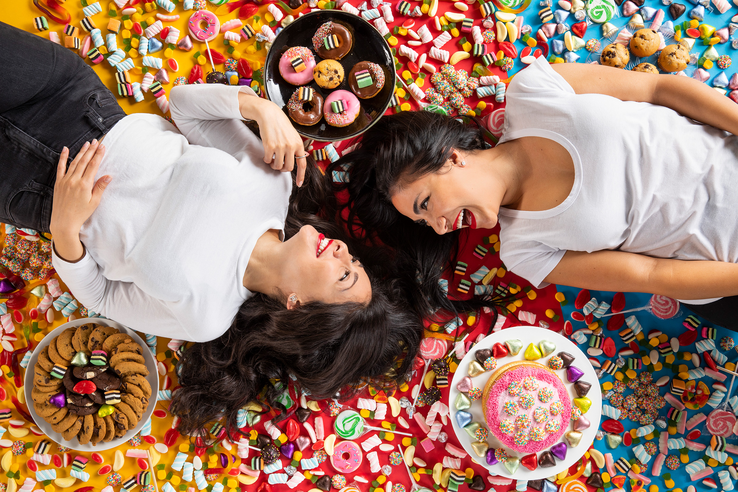 Editorial studio photography of the 2 Lick Your Phone founders surrounded by lollies and laughing at each other