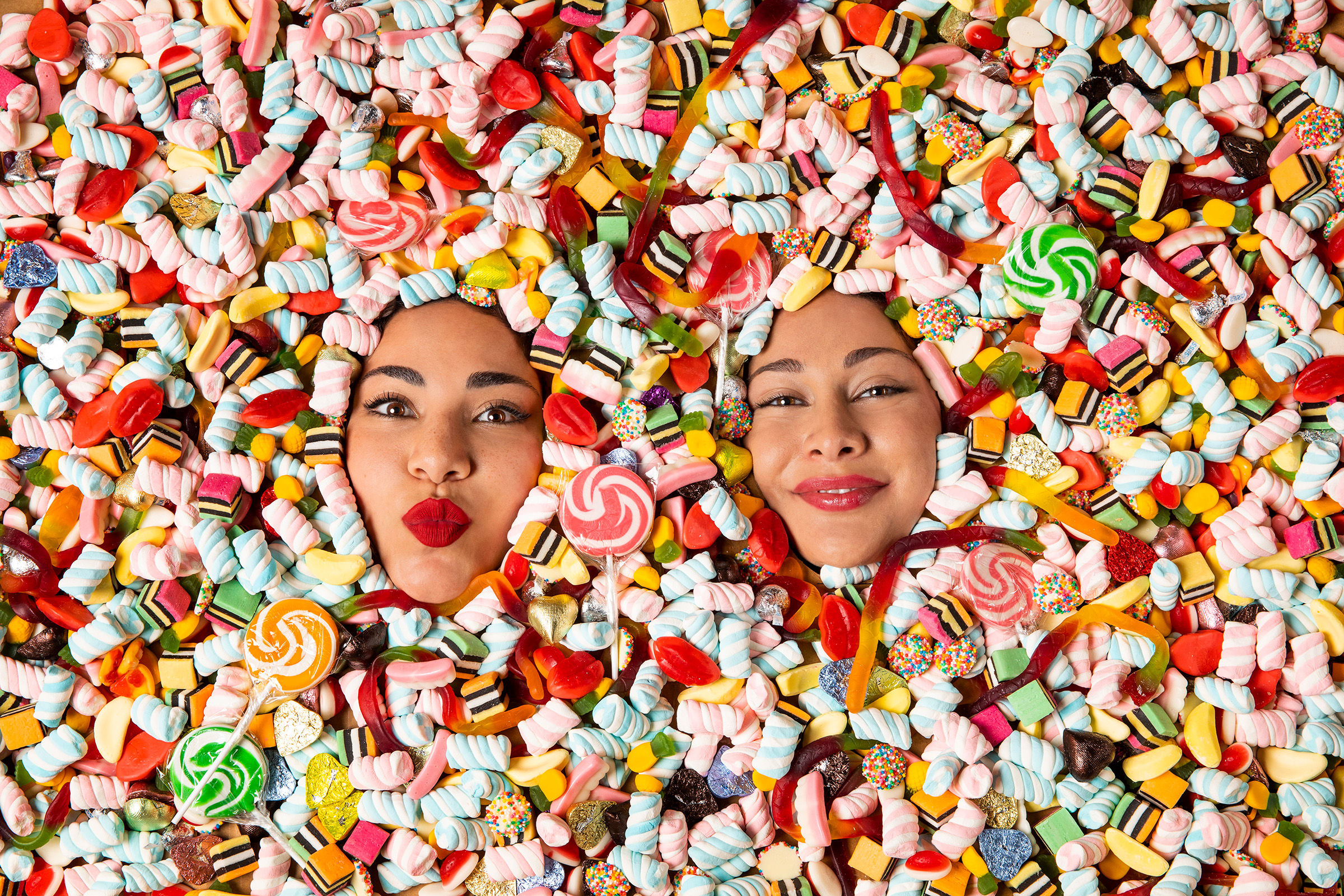 Editorial studio photography of the 2 Lick Your Phone founders covered in lollies