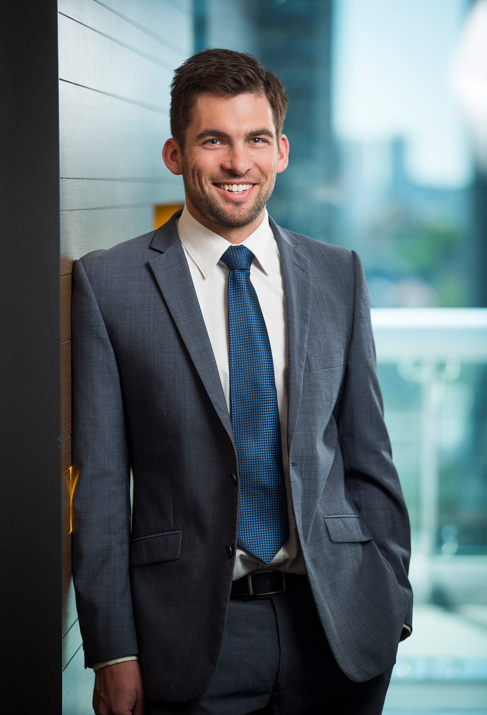 Corporate environmental lawyer portrait photography Davies Collison Cave male smiling hand in pocket office city background