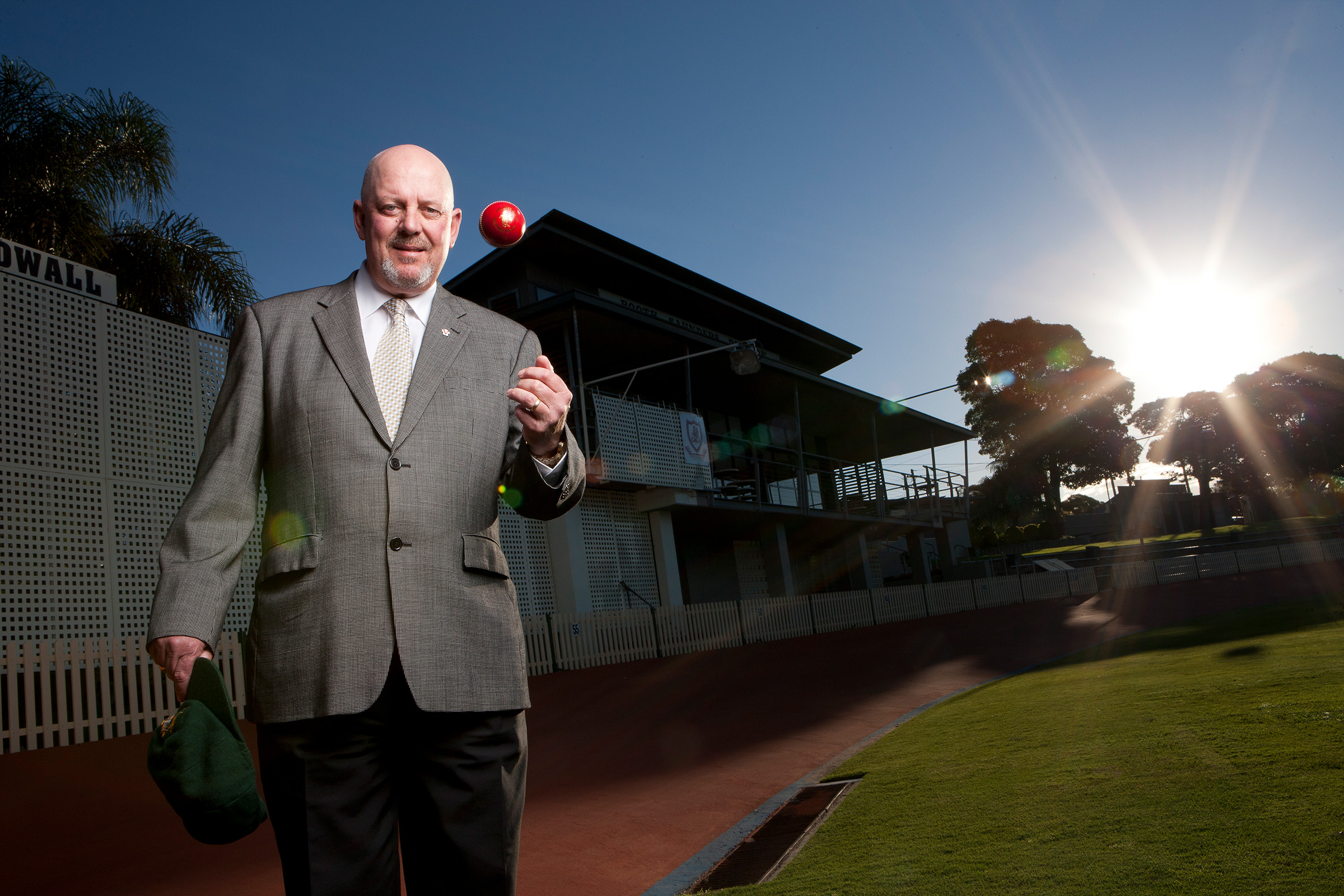 Location editorial environmental photography or Murray Bennett tossing cricket ball and holding baggy green
