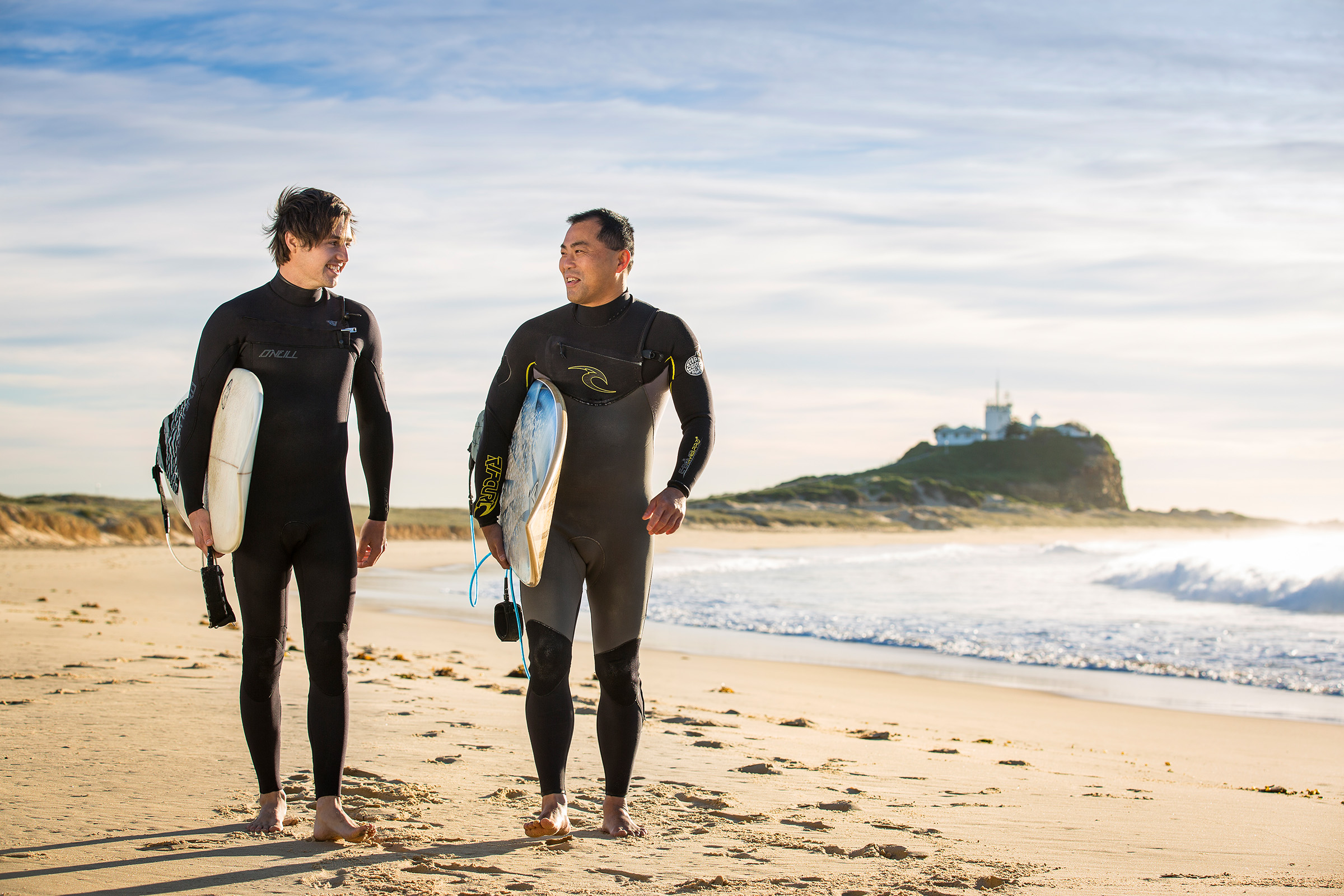 Advertising location photography for NIB of 2 surfers walking along Nobbys Beach