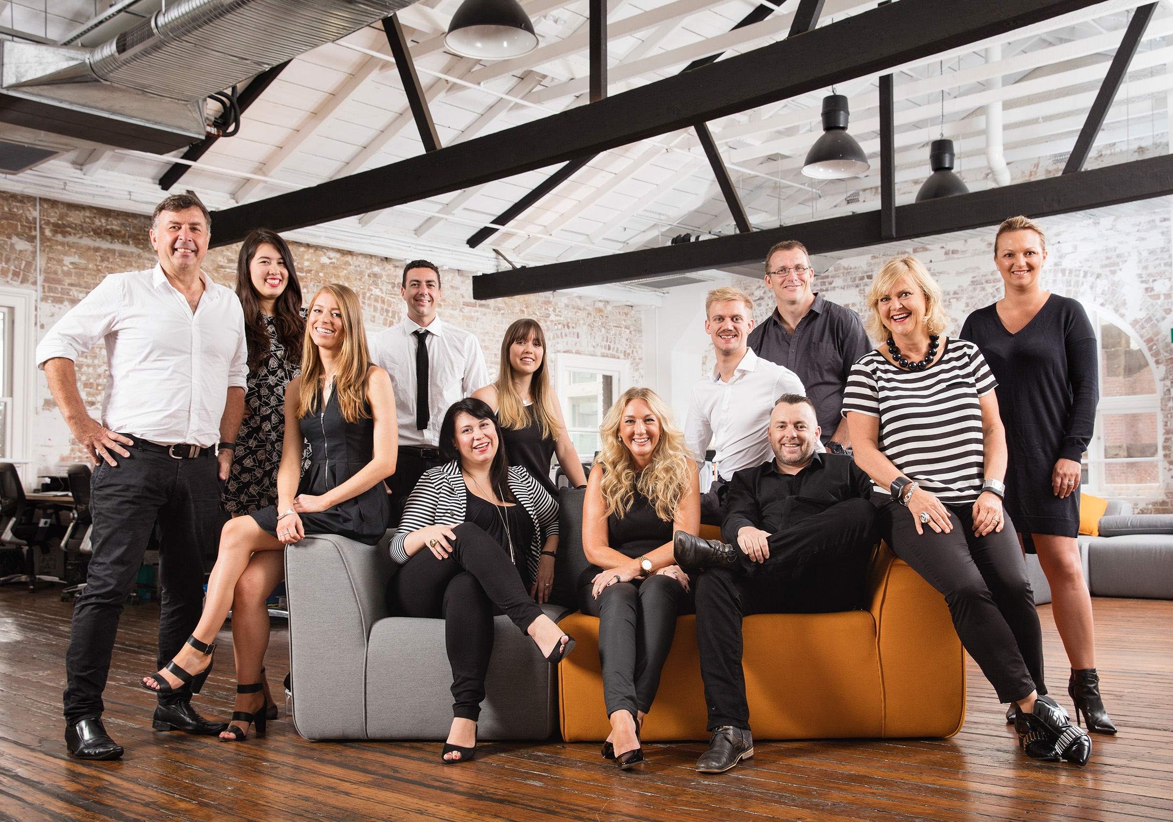 Creative staff group photography of 12 people seated and standing in a contemporary industrial office