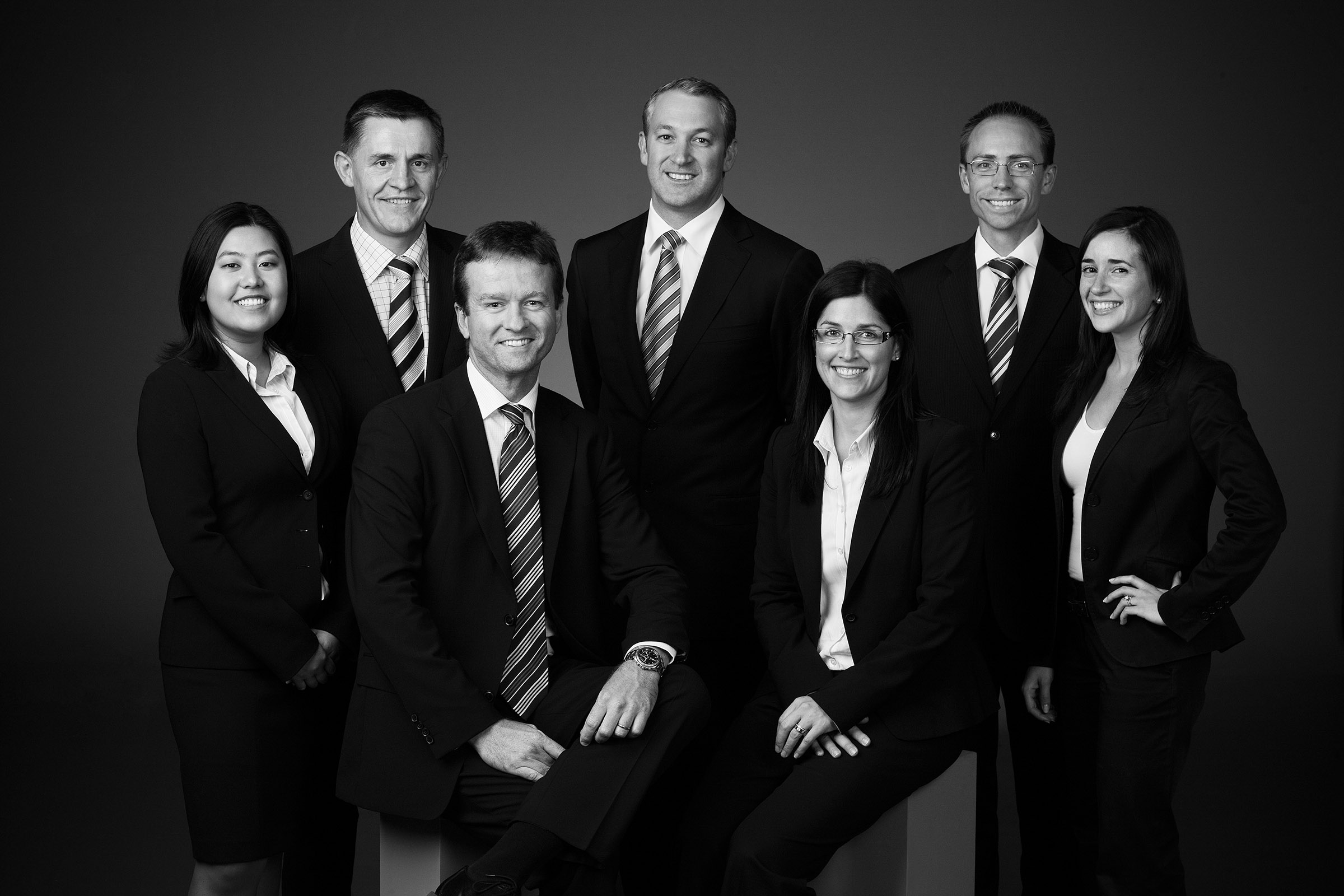 Corporate studio black and white group shot photography of 7 people standing and sitting