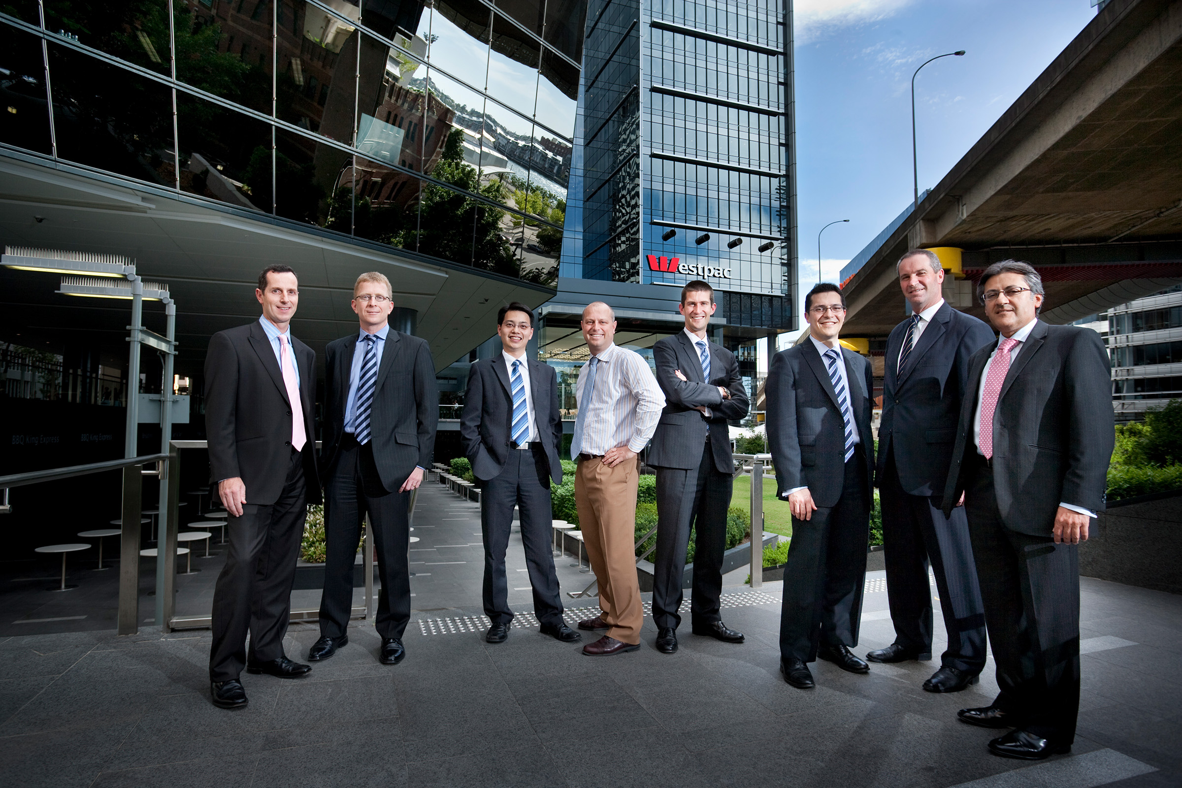 Corporate outdoor group photography 8 men standing in a row with Westpac building in background