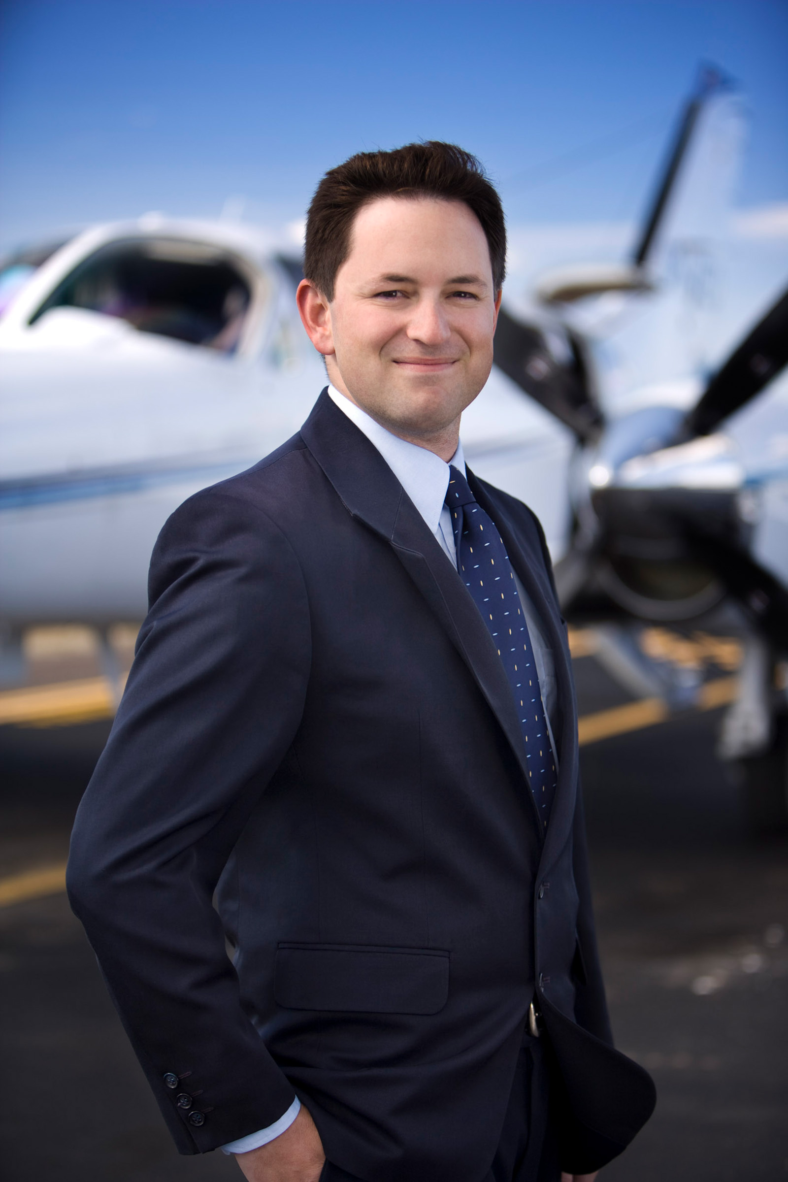 Corporate editorial location photography PWC male hands in pocket blue suit plane background