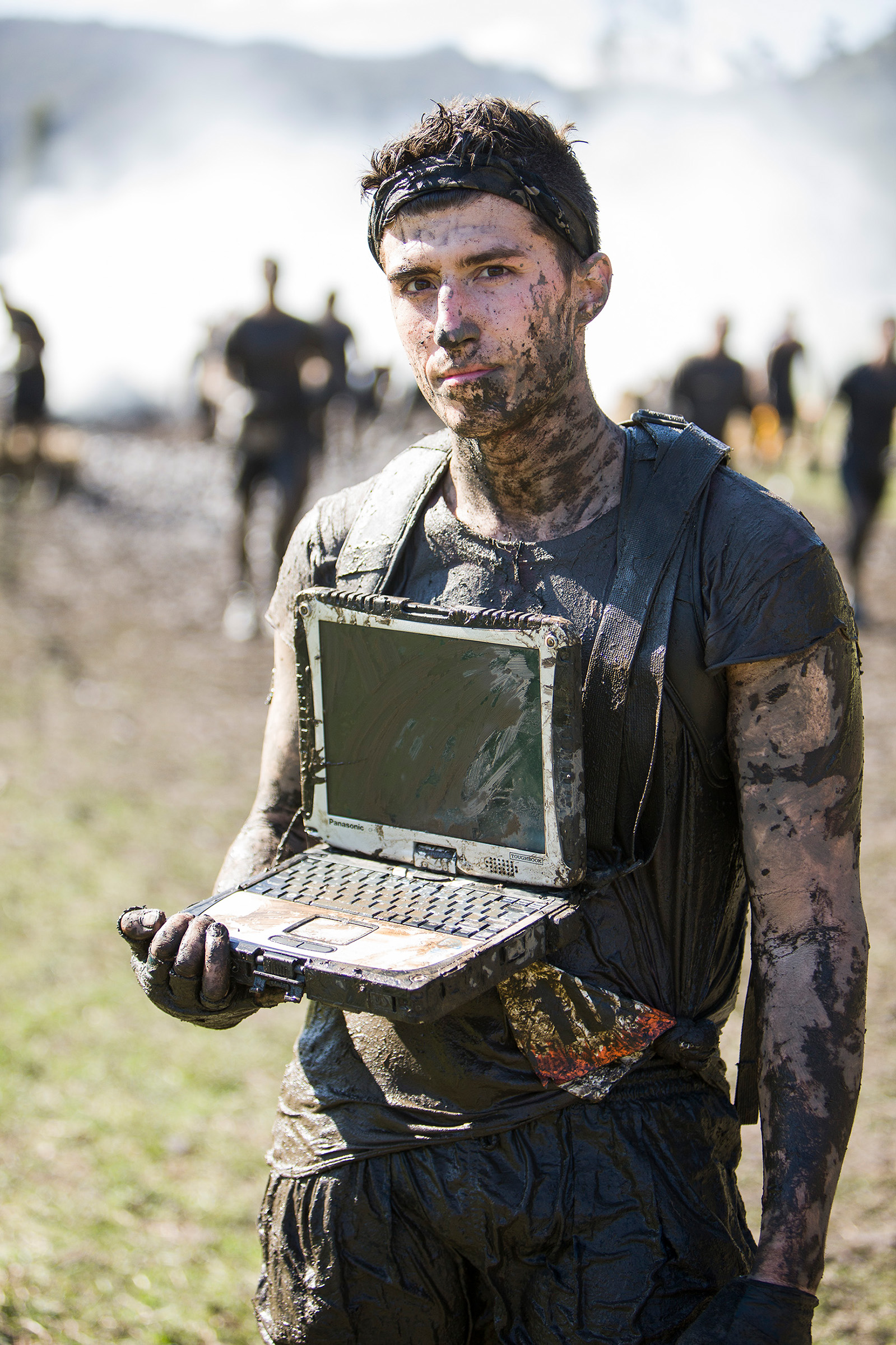 Location product photography competitor racing through mud with Panasonic Toughbook ToughMudder
