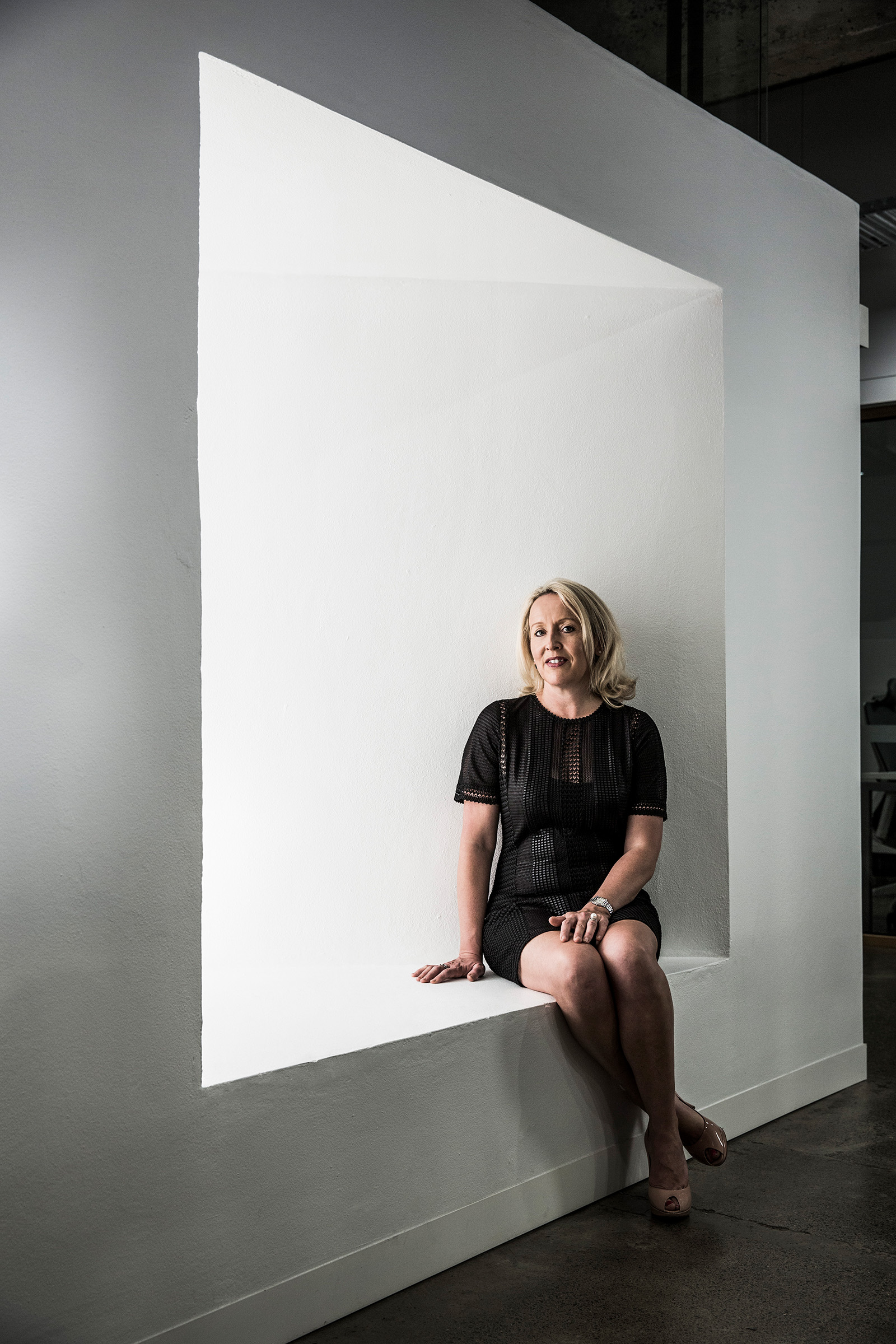 Editorial photography of Paula Kensington seated on a geometric square feature in industrial space looking at camera