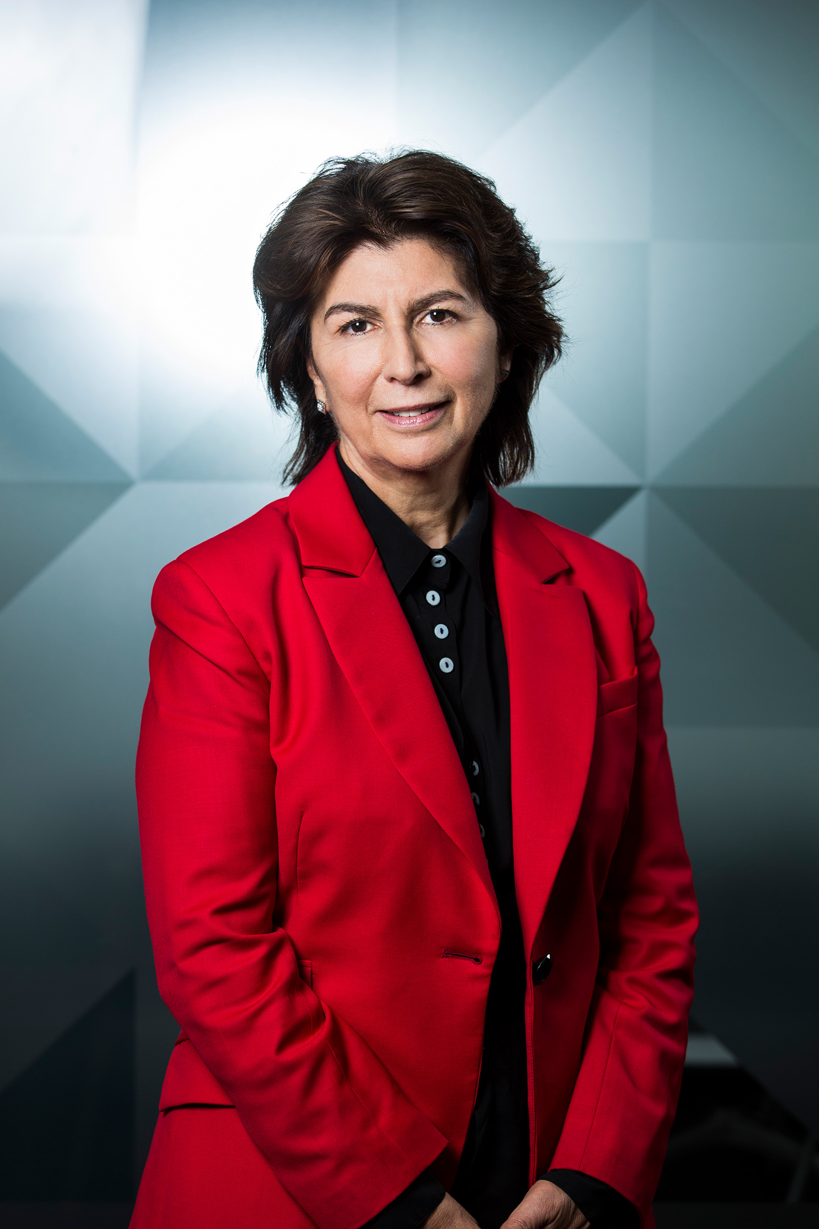 Corporate environmental photography of woman wearing black shirt red jacket against a grey triangle tessellated background