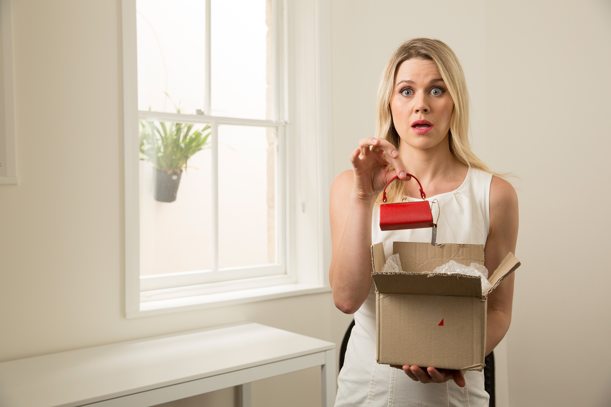 Advertising photography for PayPal of surprised woman receiving too small handbag she ordered online