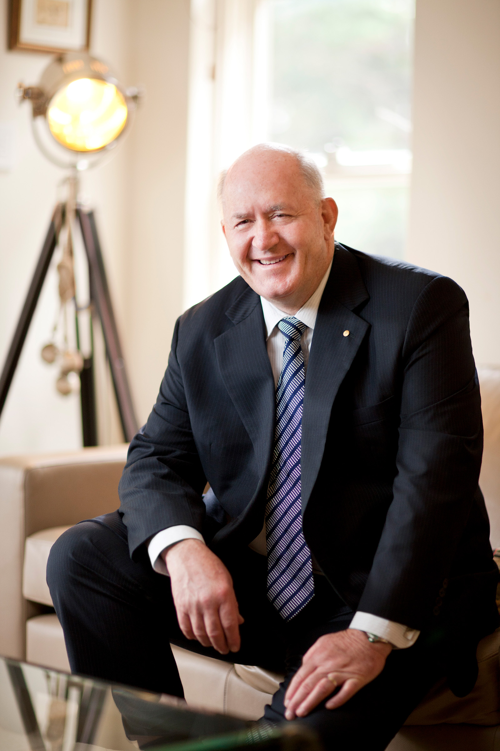 Editorial corporate location photography of a smiling Peter Cosgrove sitting on a couch in a living room
