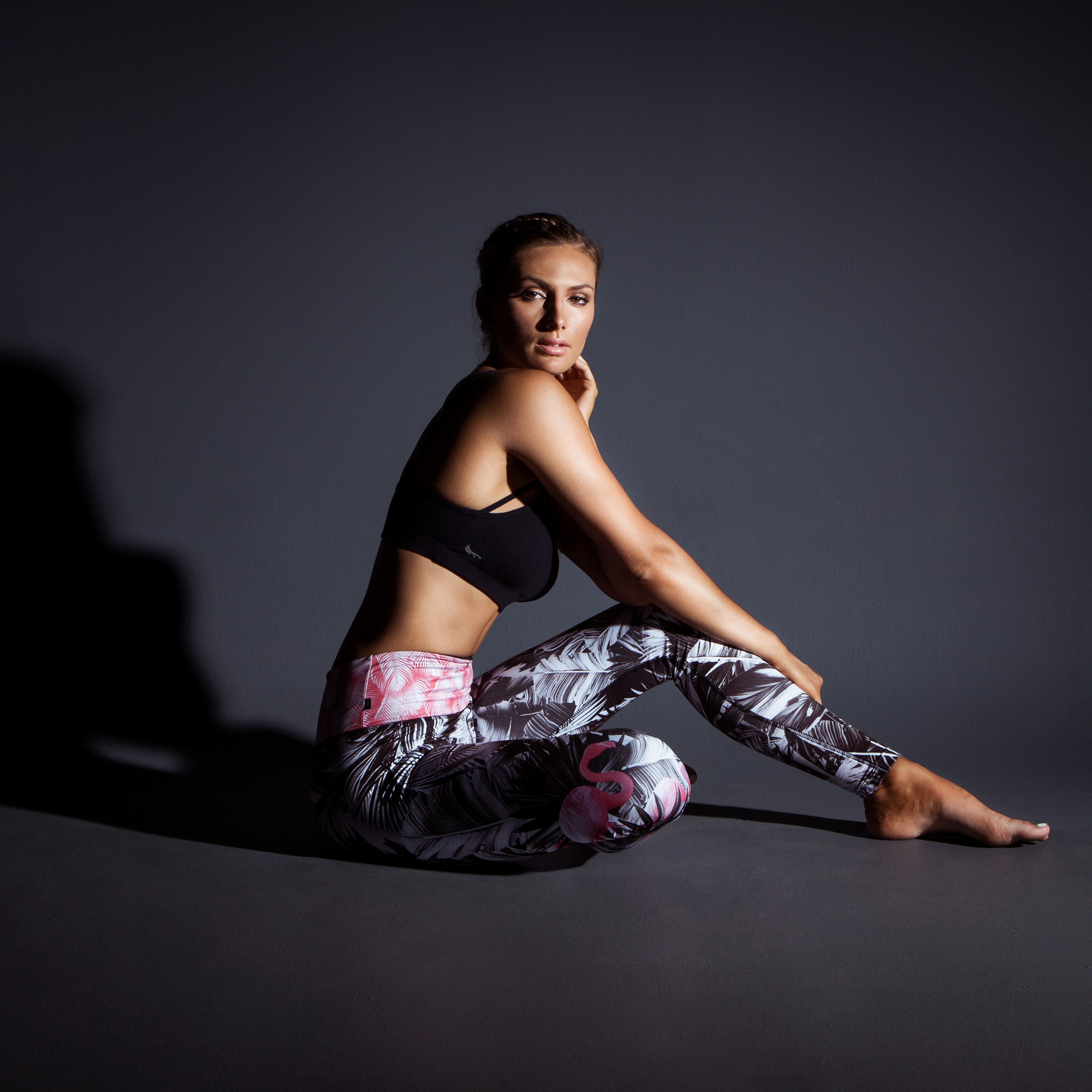 Fashion studio photography model sitting in black top and print pants dark moody background