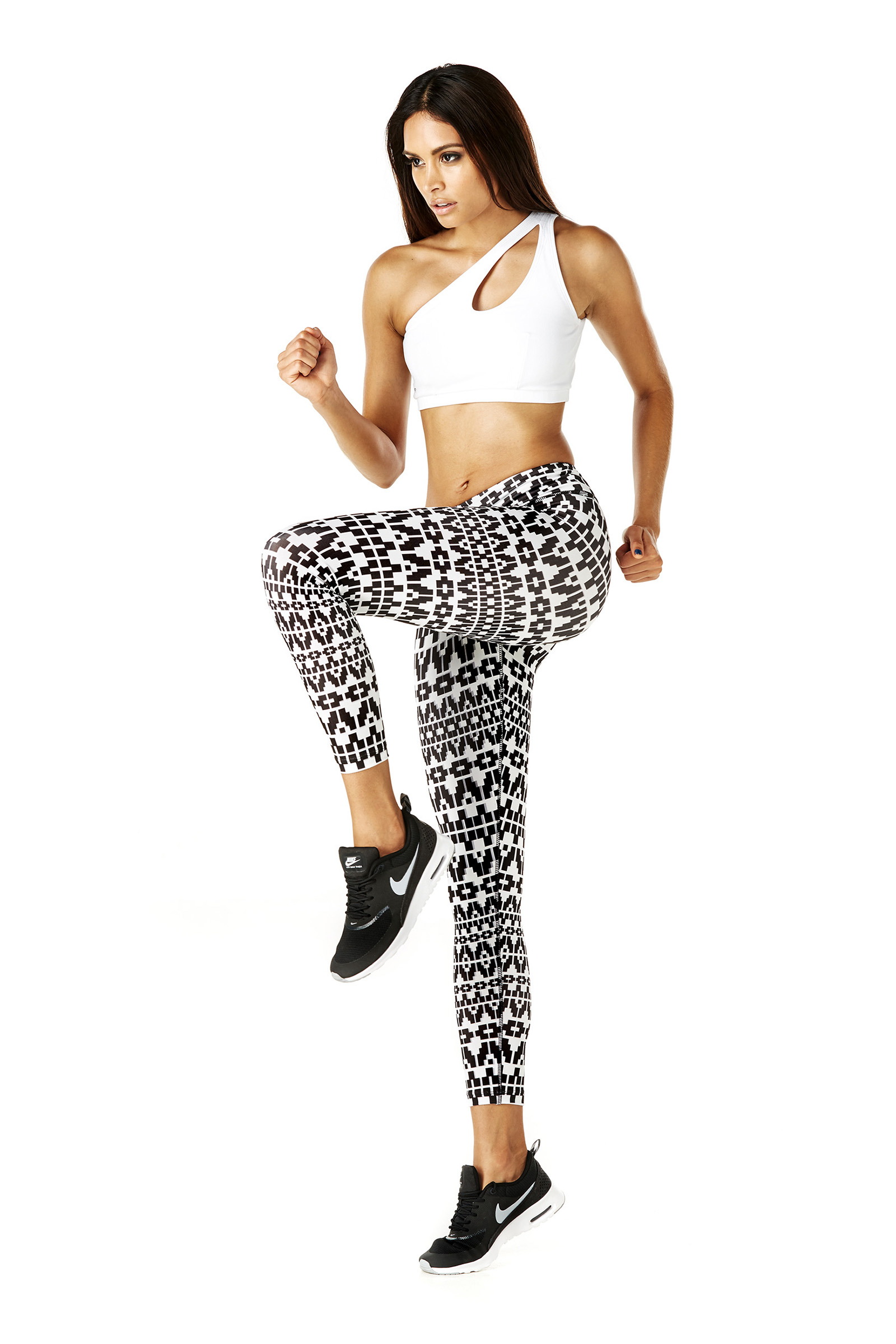 Fashion studio photography of fitness model in white top and black and white pants workout pose