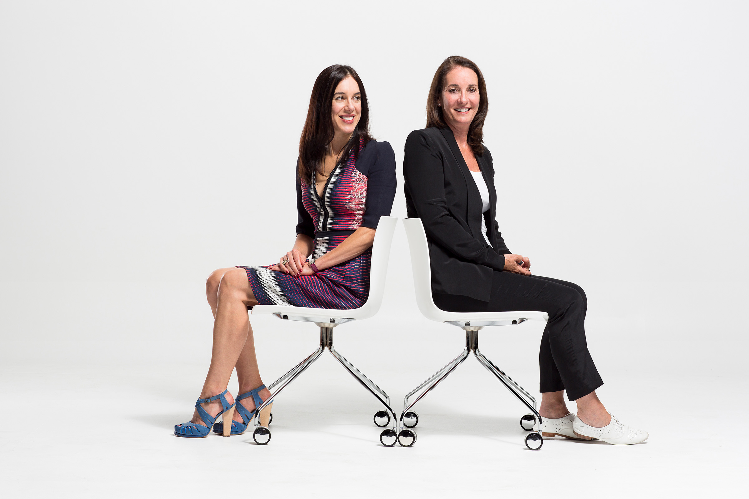 Corporate editorial studio photography REINSW 2 females seated white chairs white background