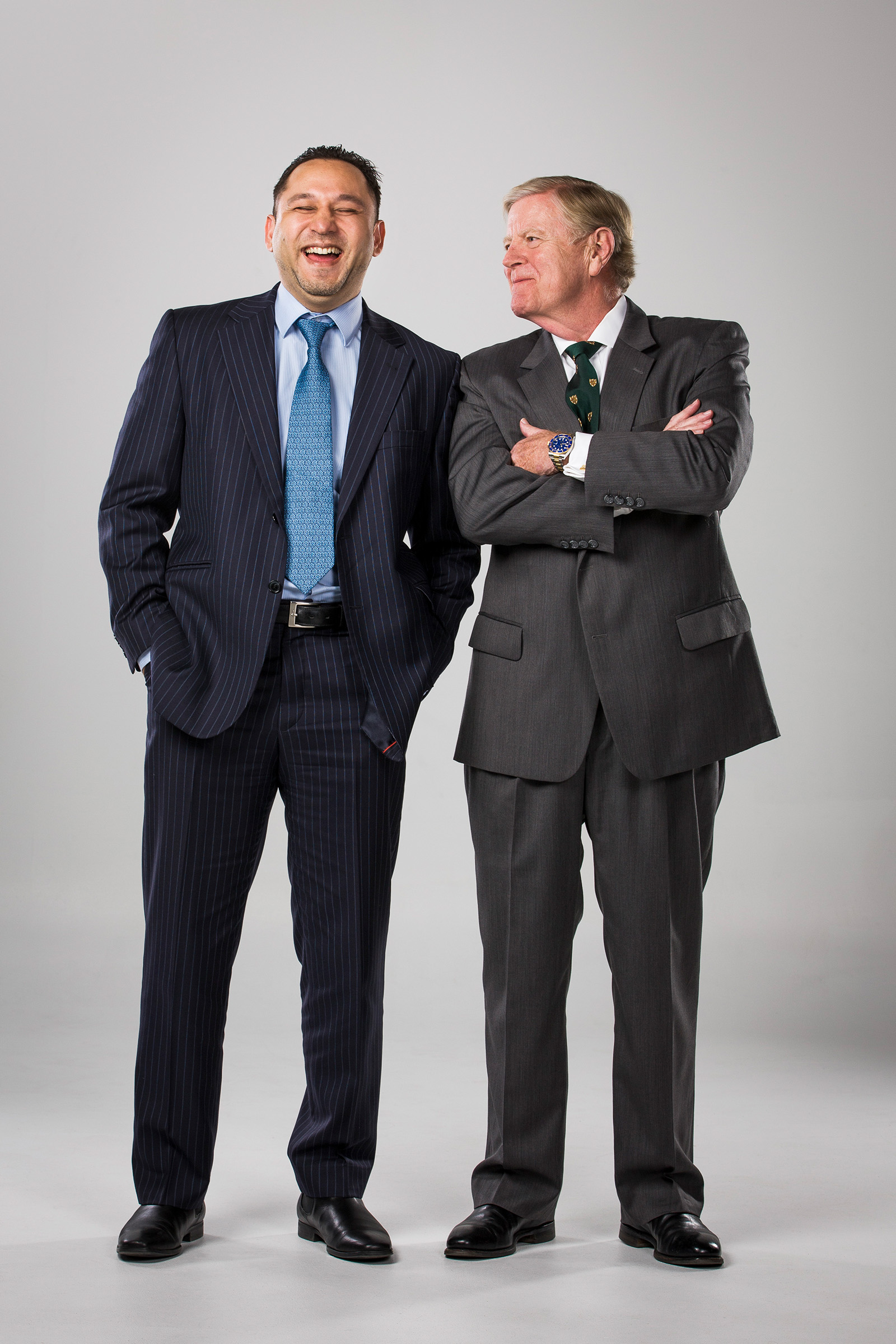 Corporate editorial studio photography of 2 men laughing wearing suit and ties