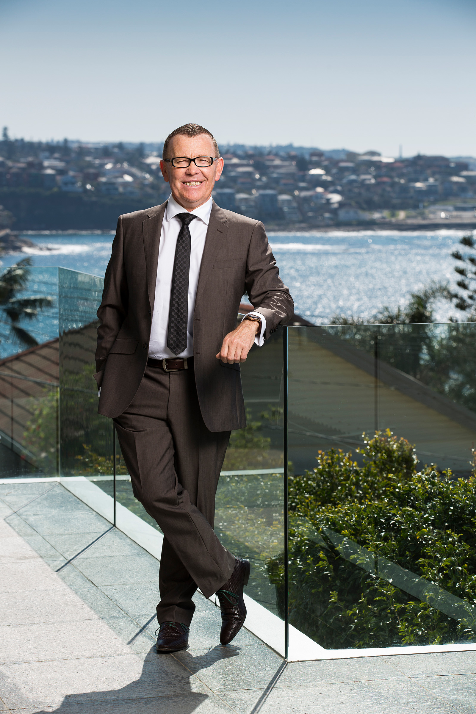 Editorial outdoor photography of smiling male auctioneer leaning on glass balustrade with water view background