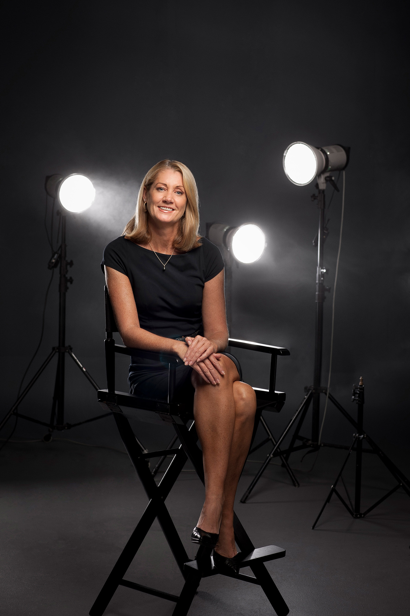 Corporate editorial studio photography REINSW female seated directors chair flashes background