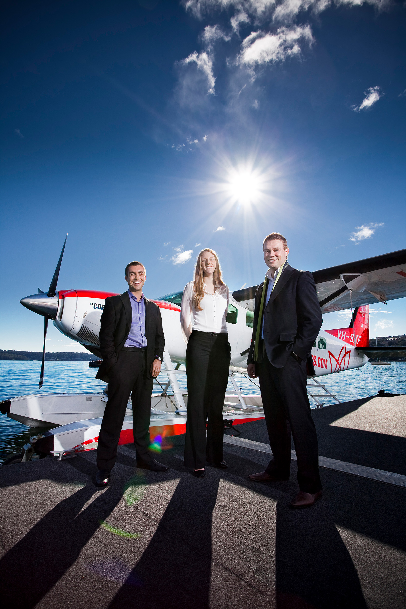 Editorial industry location photography of 3 people on wharf with seaplane on the water in the background