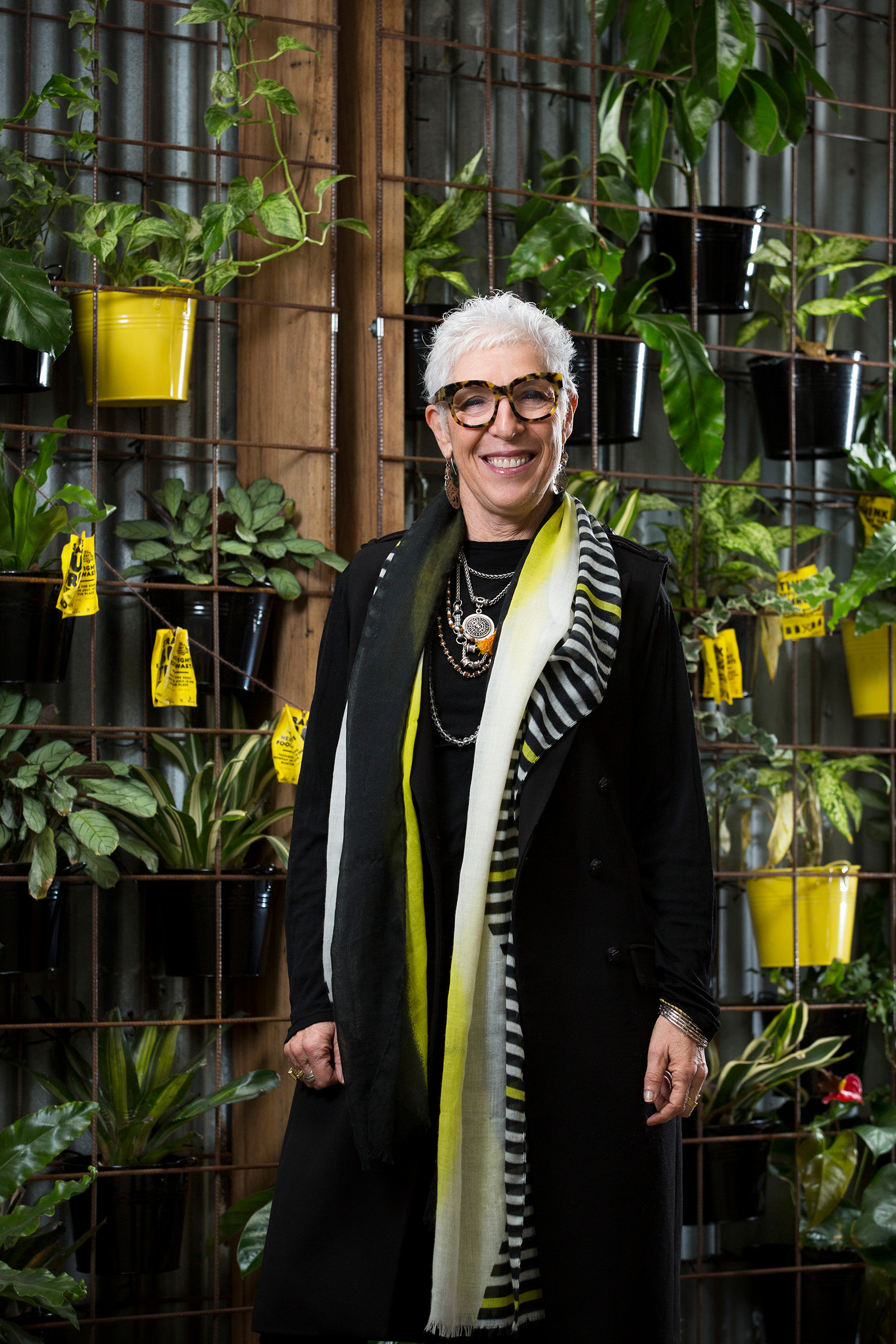 Editorial photography of Ronni Kahn Oz Harvest in front of vertical garden green wall different angle
