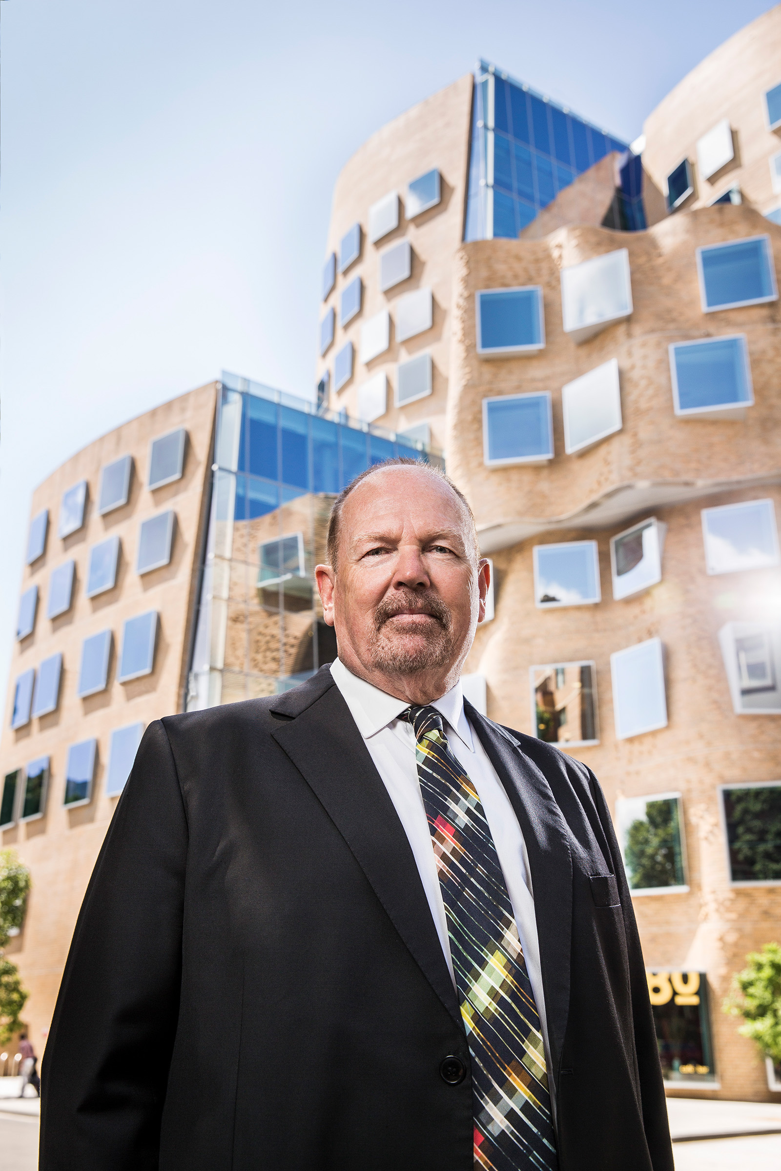 Corporate editorial photography of Ross Milbourne President of UTS with curvy building in the background