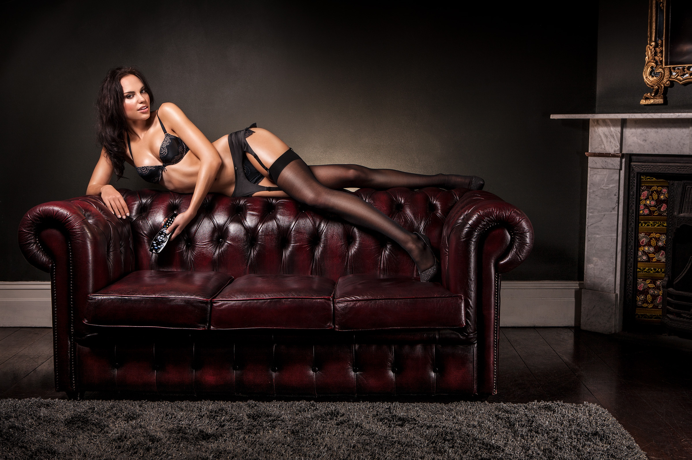 Adverting campaign photography for SBS World Movies of brunette in black lingerie on Chesterfield sofa in front of fireplace location photography