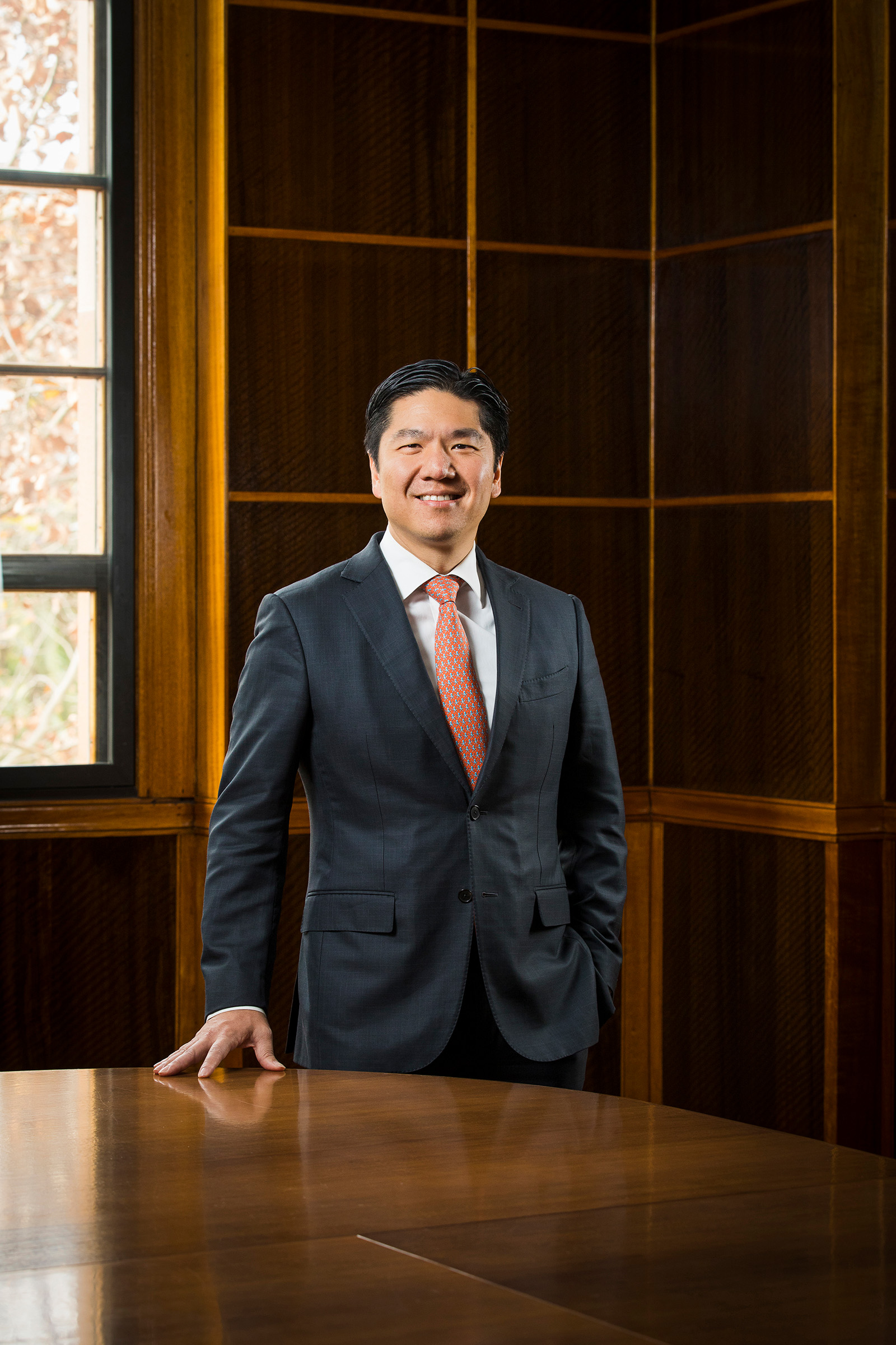 Corporate editorial annual report photography Seng Huang Lee smiling standing hand on pocket in boardroom