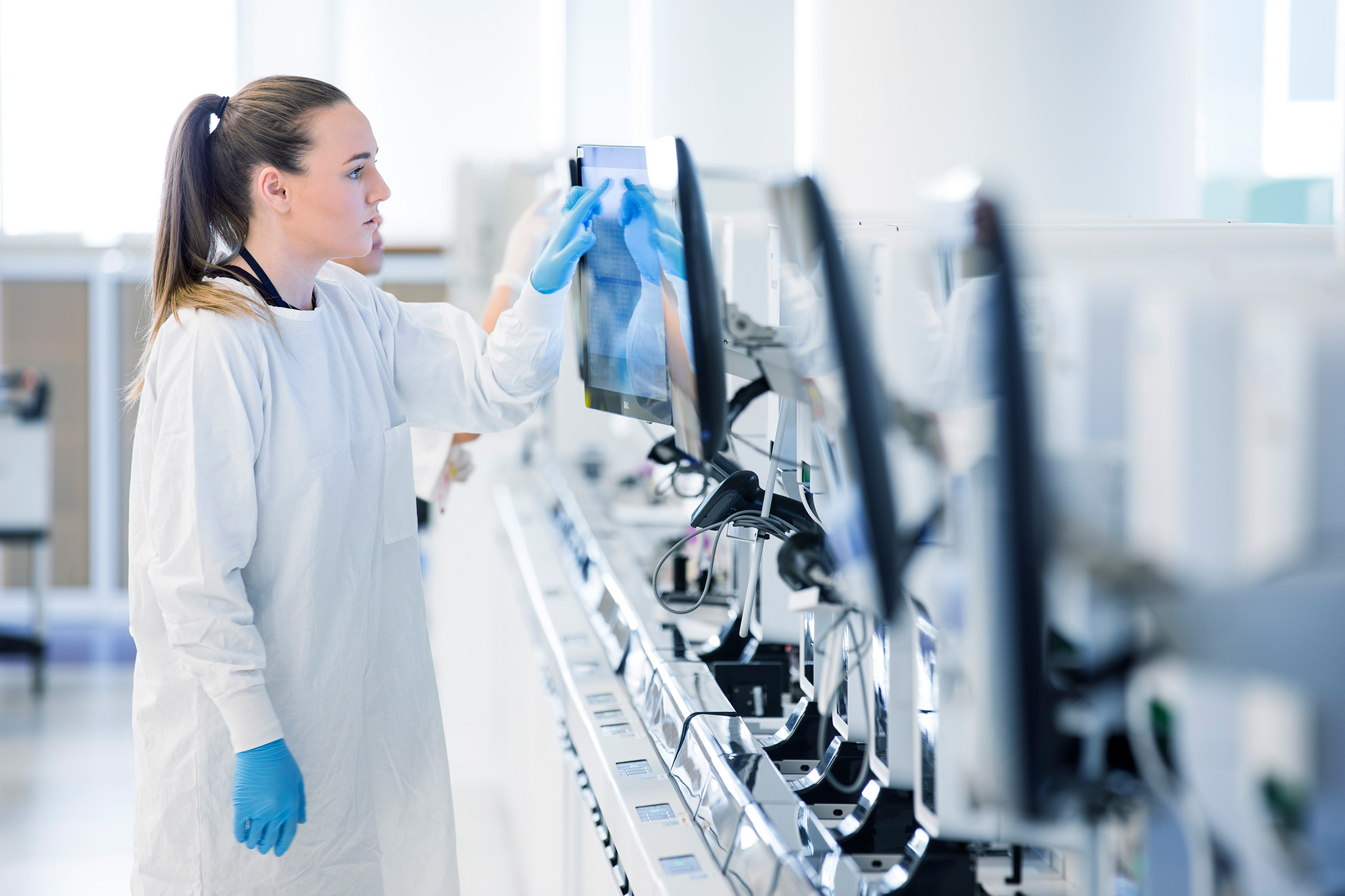 Corporate photography Sonic Healthcare Annual Report female wearing white lab coat blue gloves at touchscreen