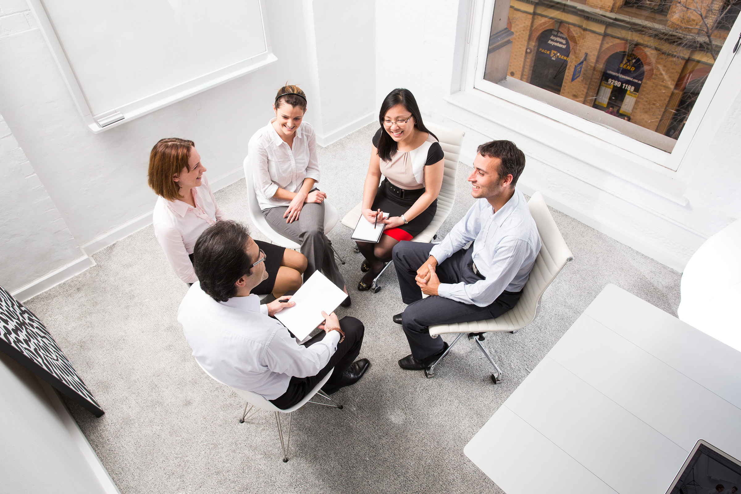 Corporate editorial location photography three woman two men seated in office have a conversation on white chairs