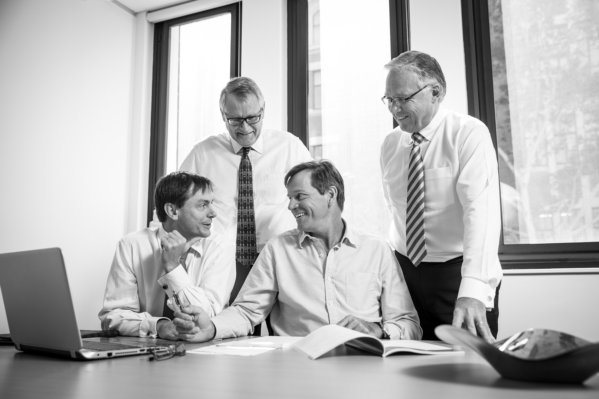 Corporate editorial photography working collaborating team of four men in an office infant of laptop