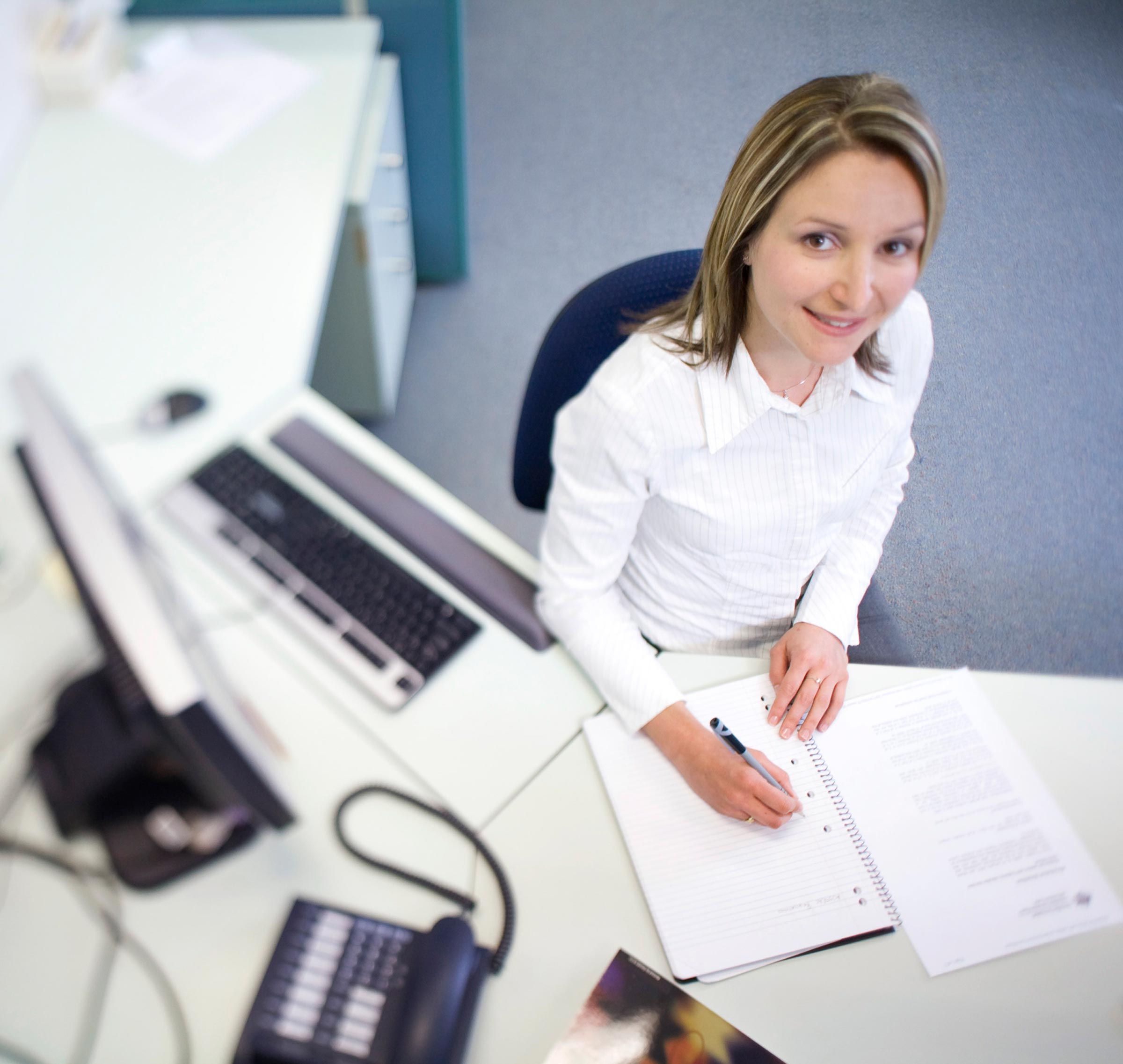 female office worker at desk writing in notebook