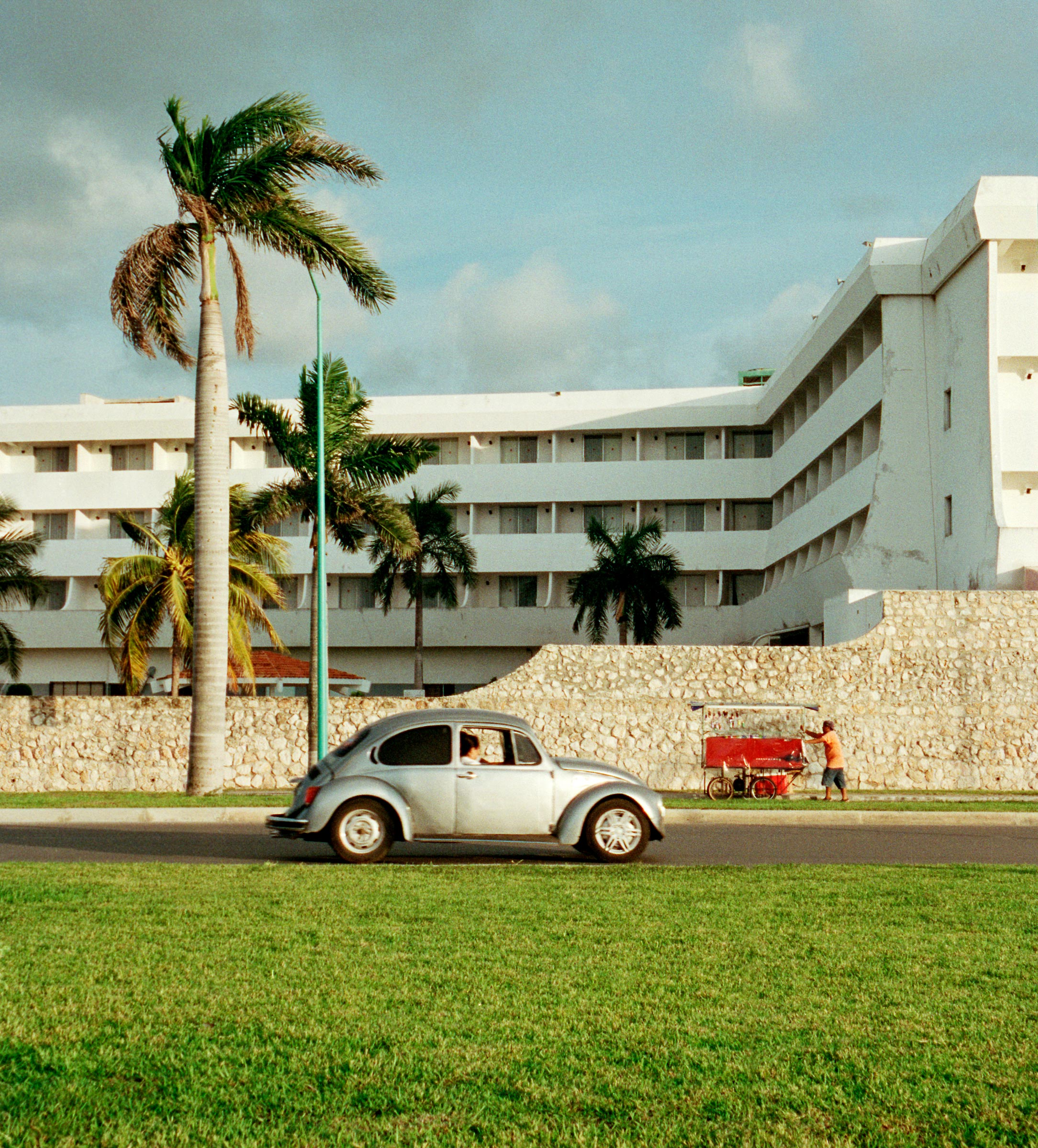 silver vw beetle driving past white hotel and palm trees