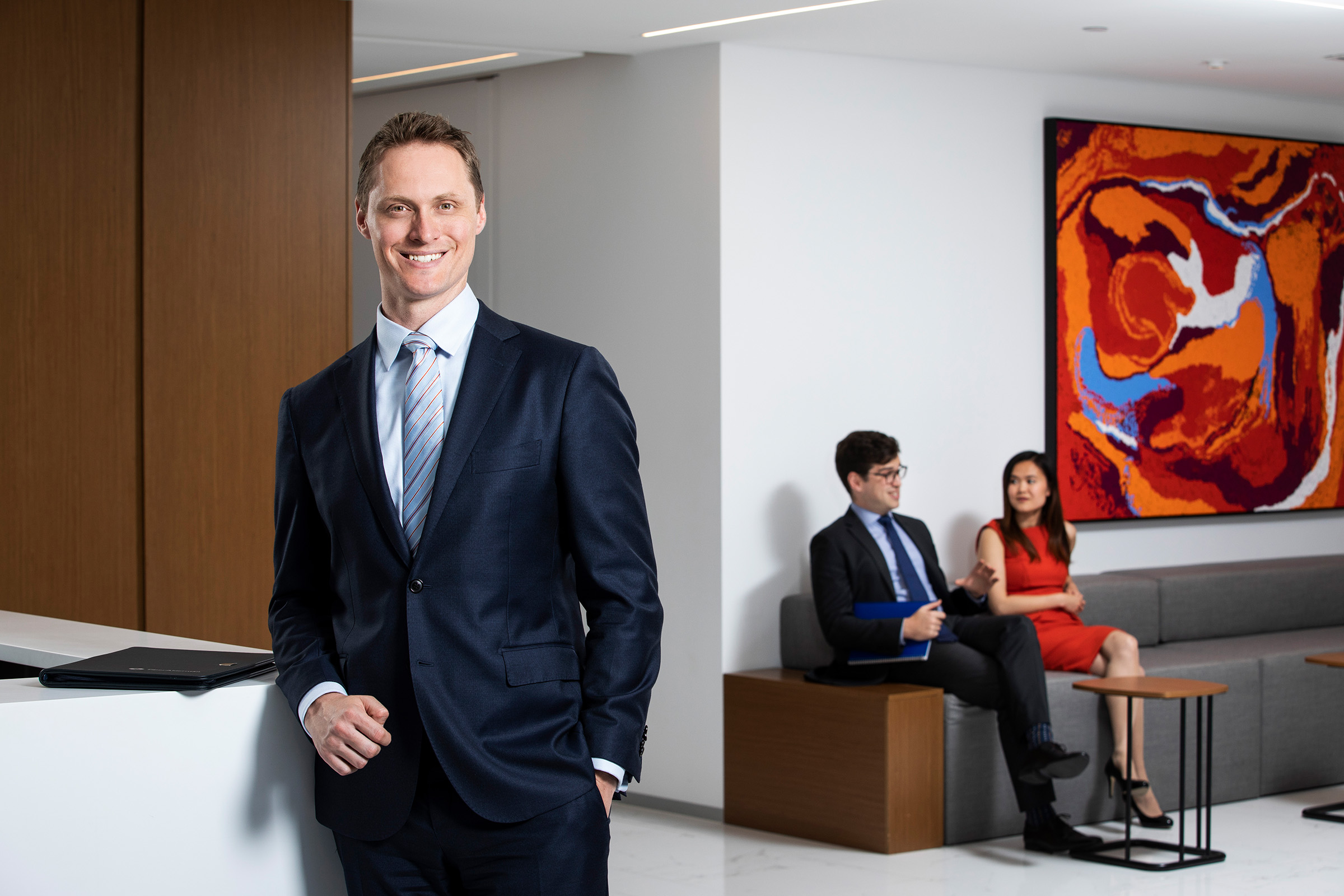 man standing and man and woman sitting in office reception area
