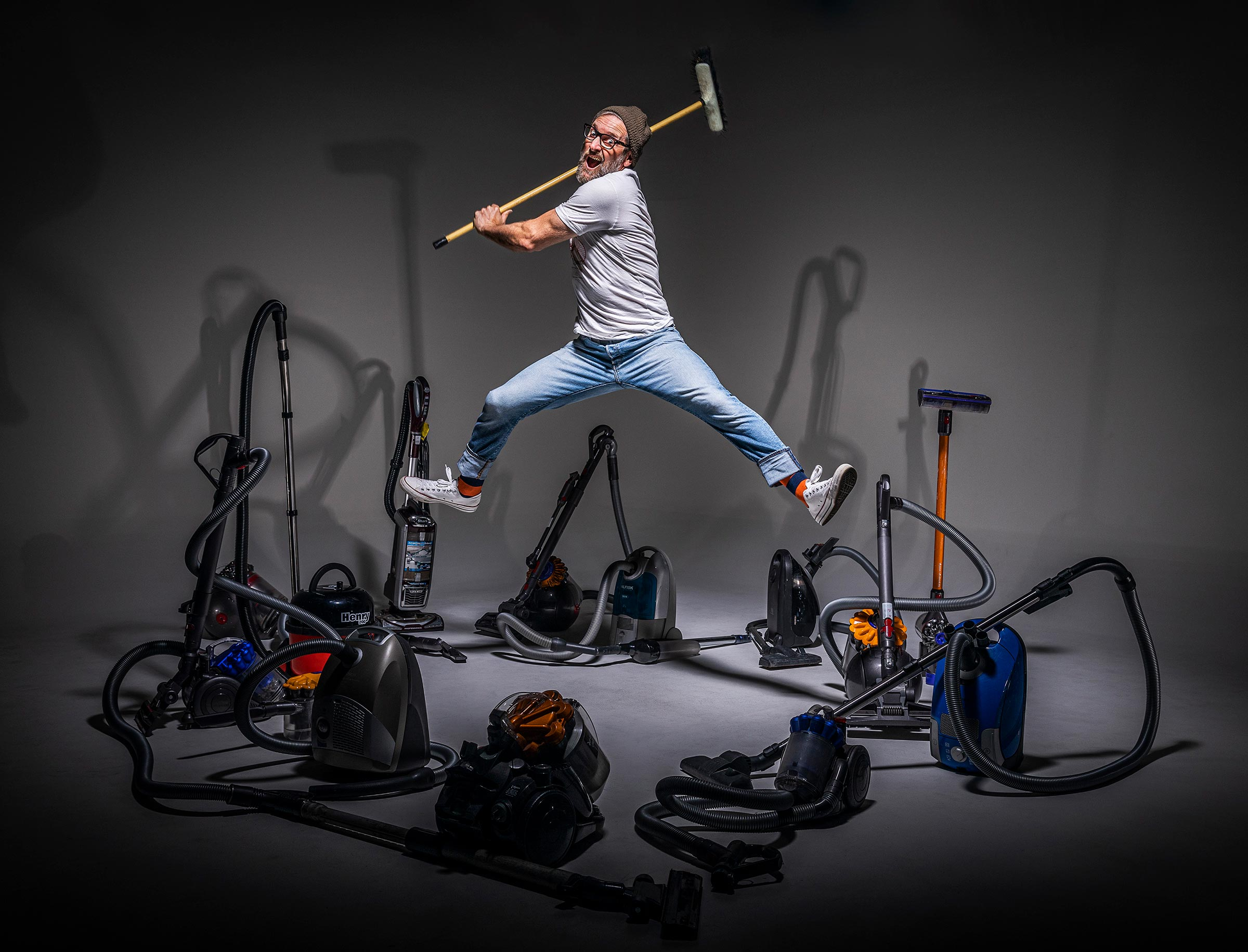 man holding a broom about to hit many vacuum cleaners