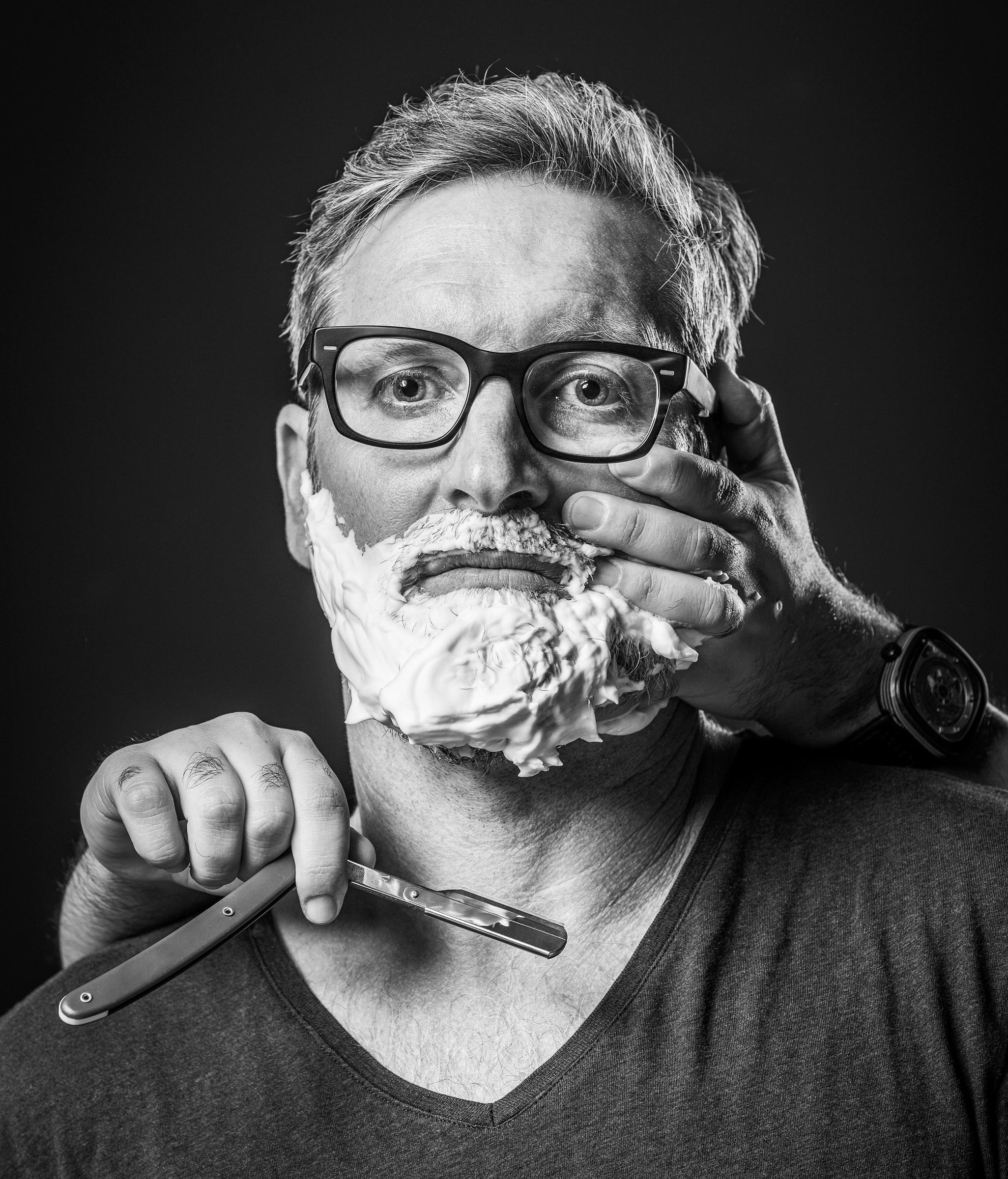 Character black and white photography of man with glasses having a n shave with cut throat