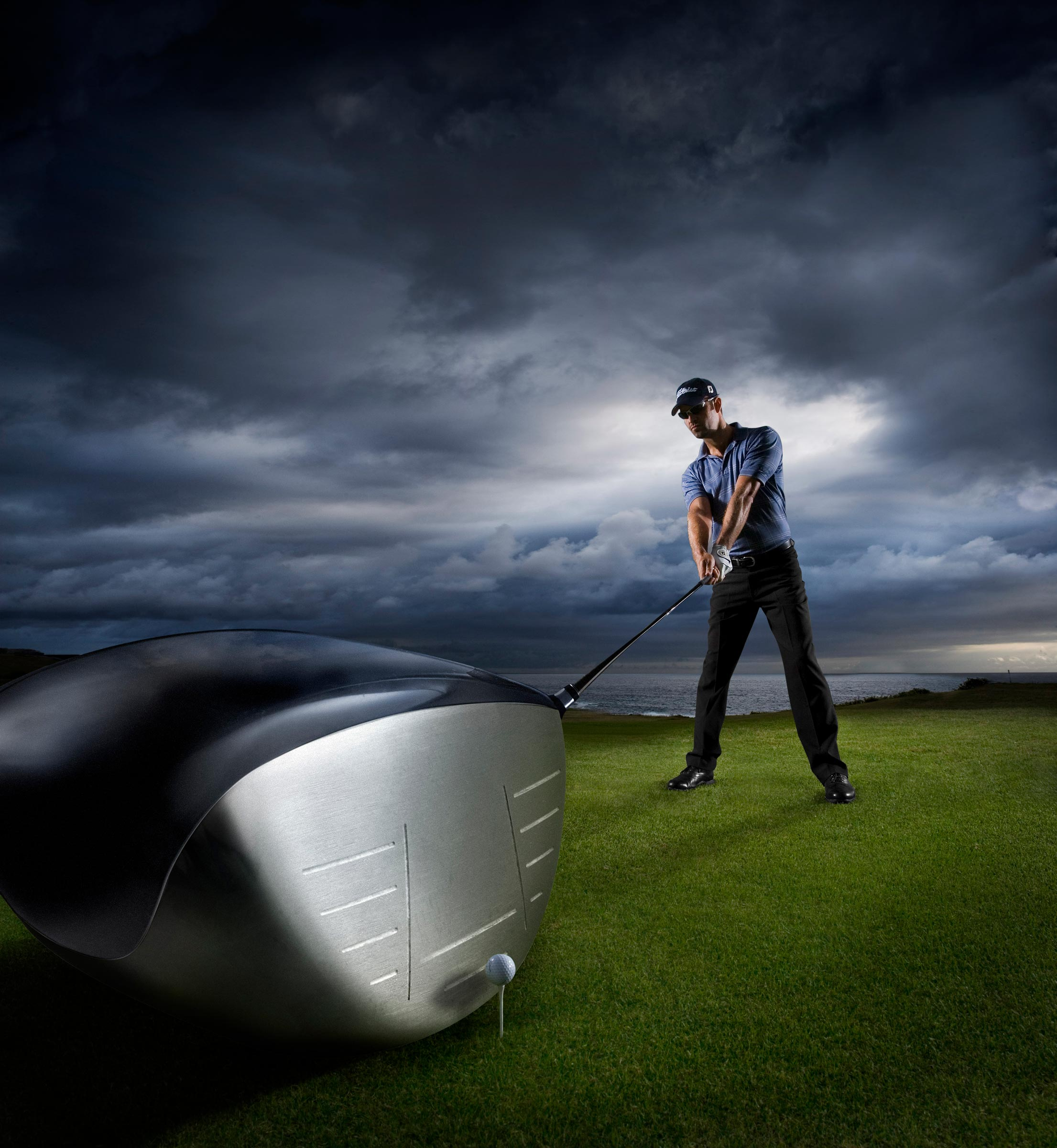golfer teeing up with storm clouds behind