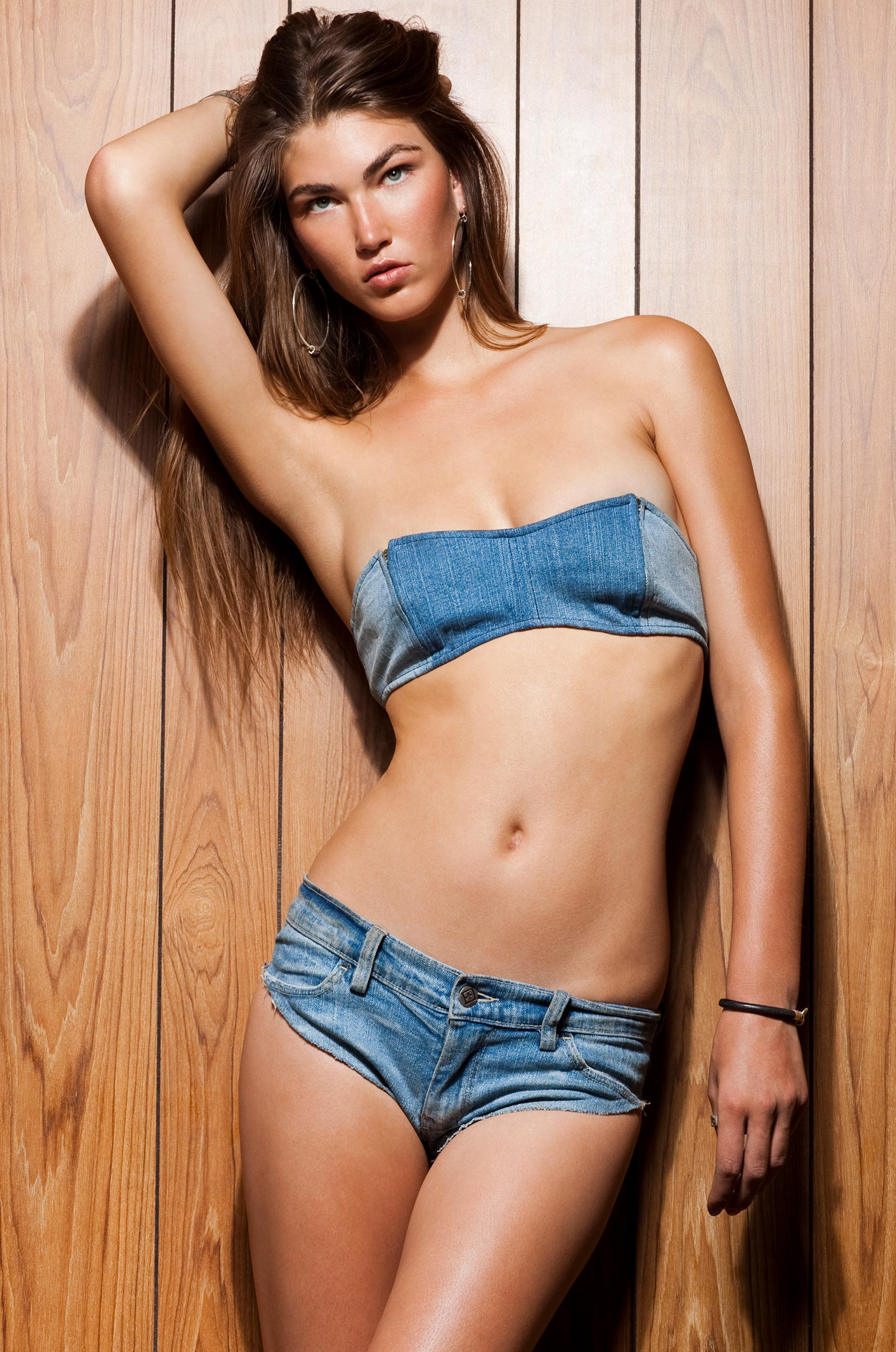 woman in denim bikini leaning against wood panel wall