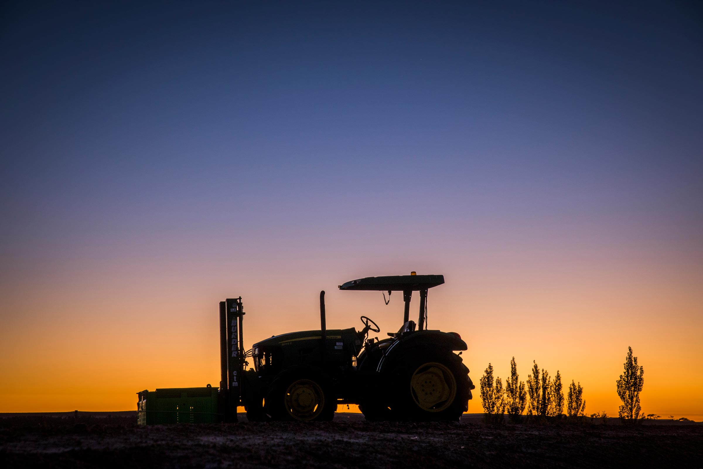 silhouette of tractor on a farm at sunrise