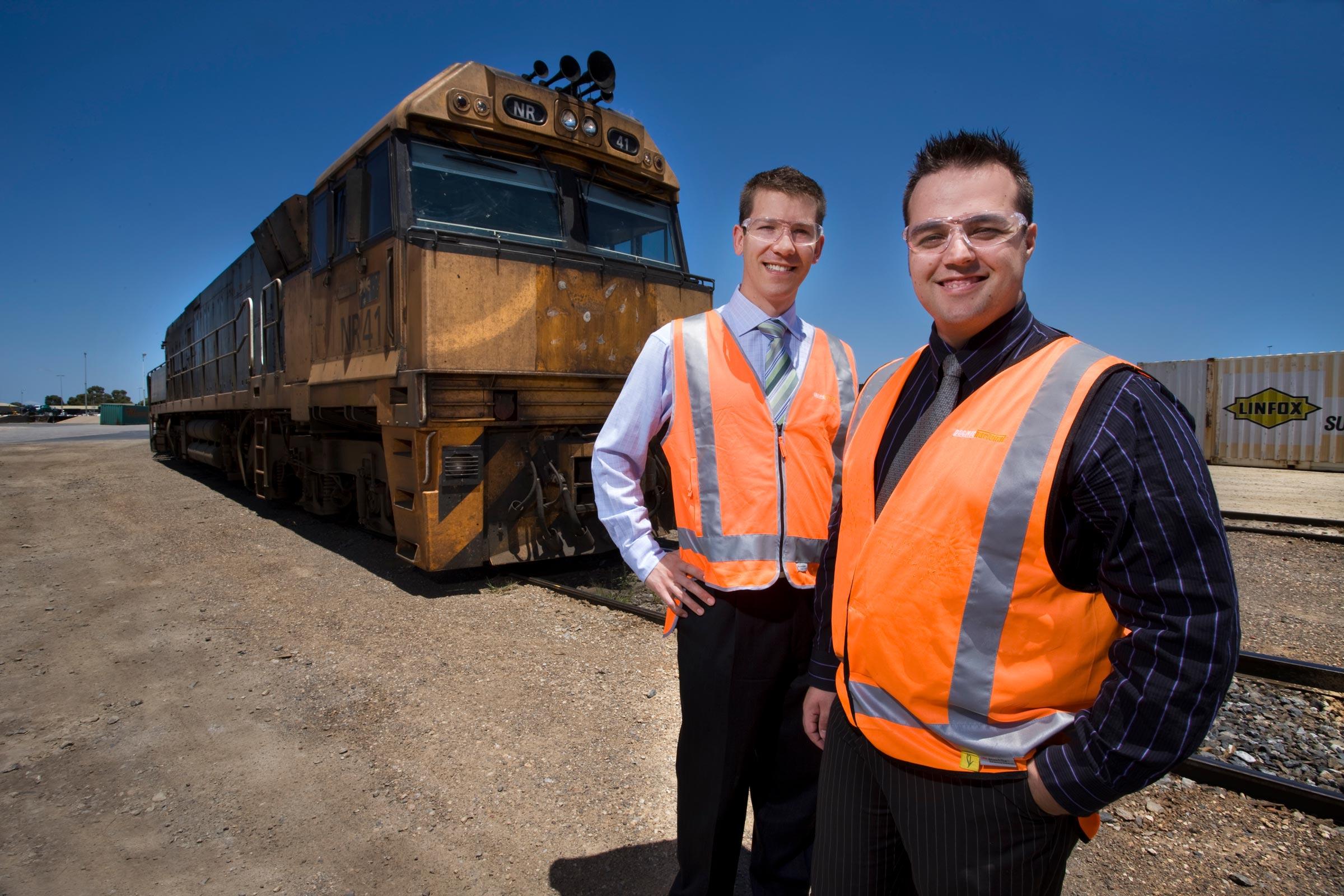 2 men wearing vests standing beside a freight train