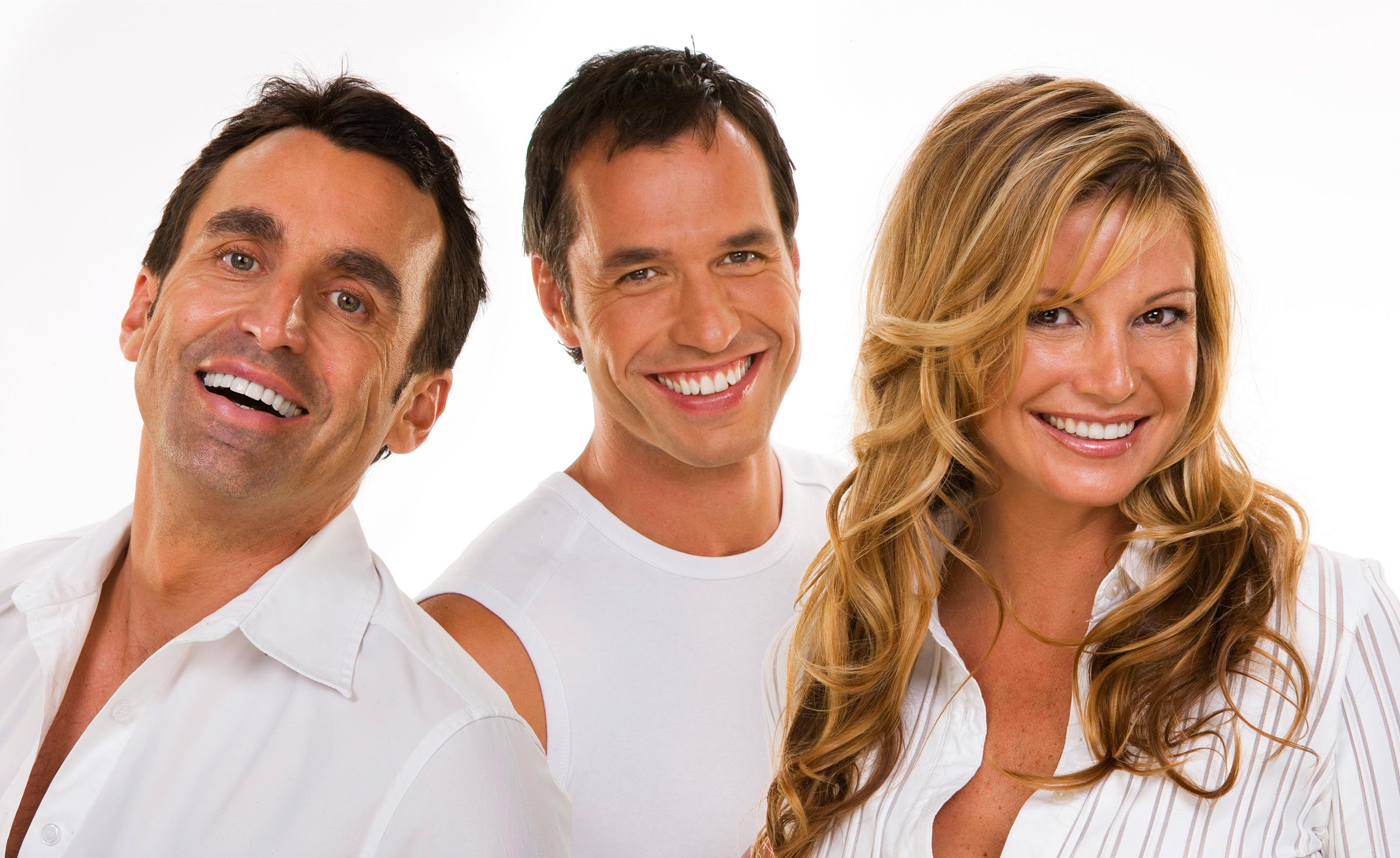 three people wearing white smiling at camera with white teeth