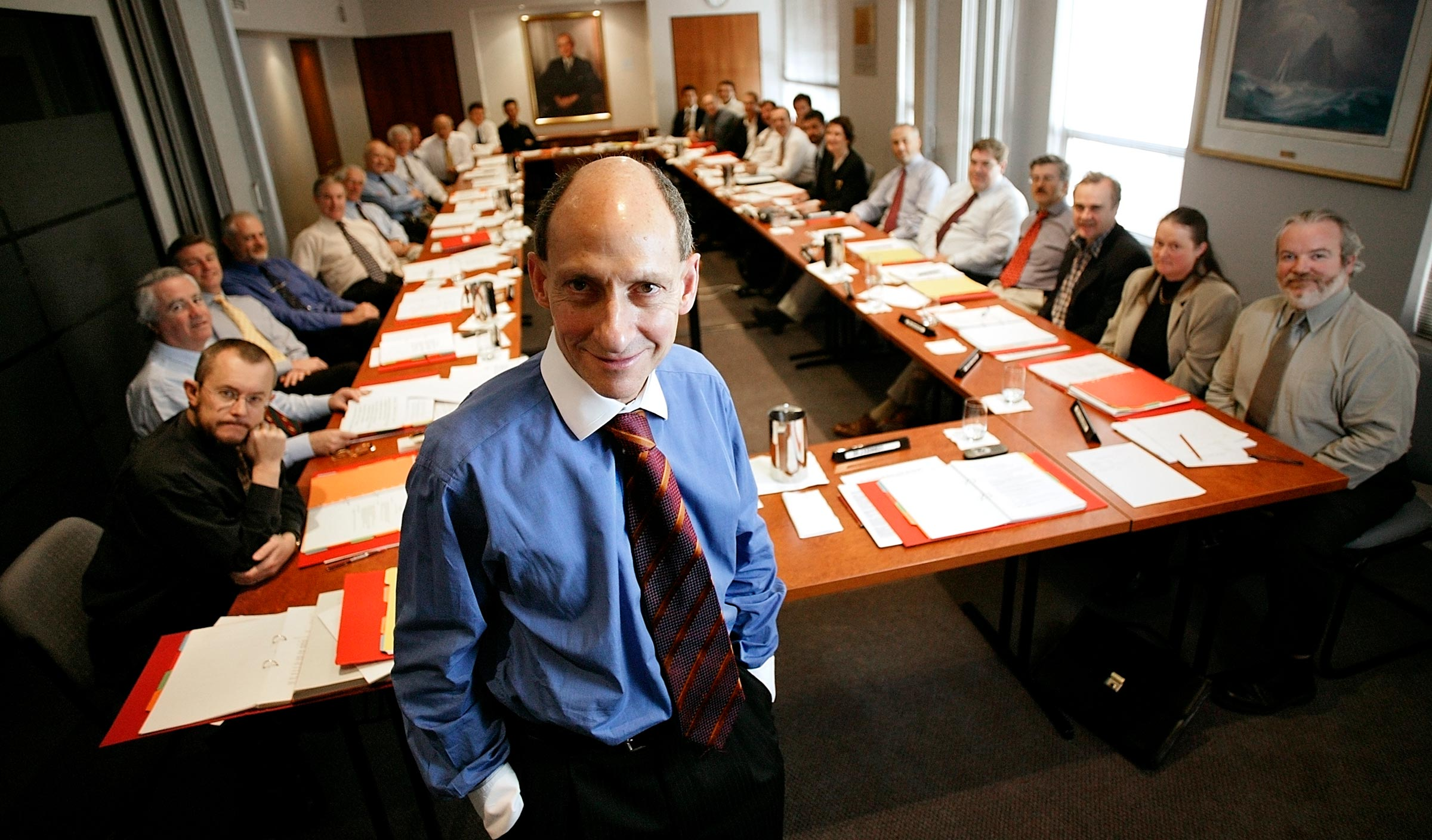 large group of people sitting around a boardroom table with boss in foreground