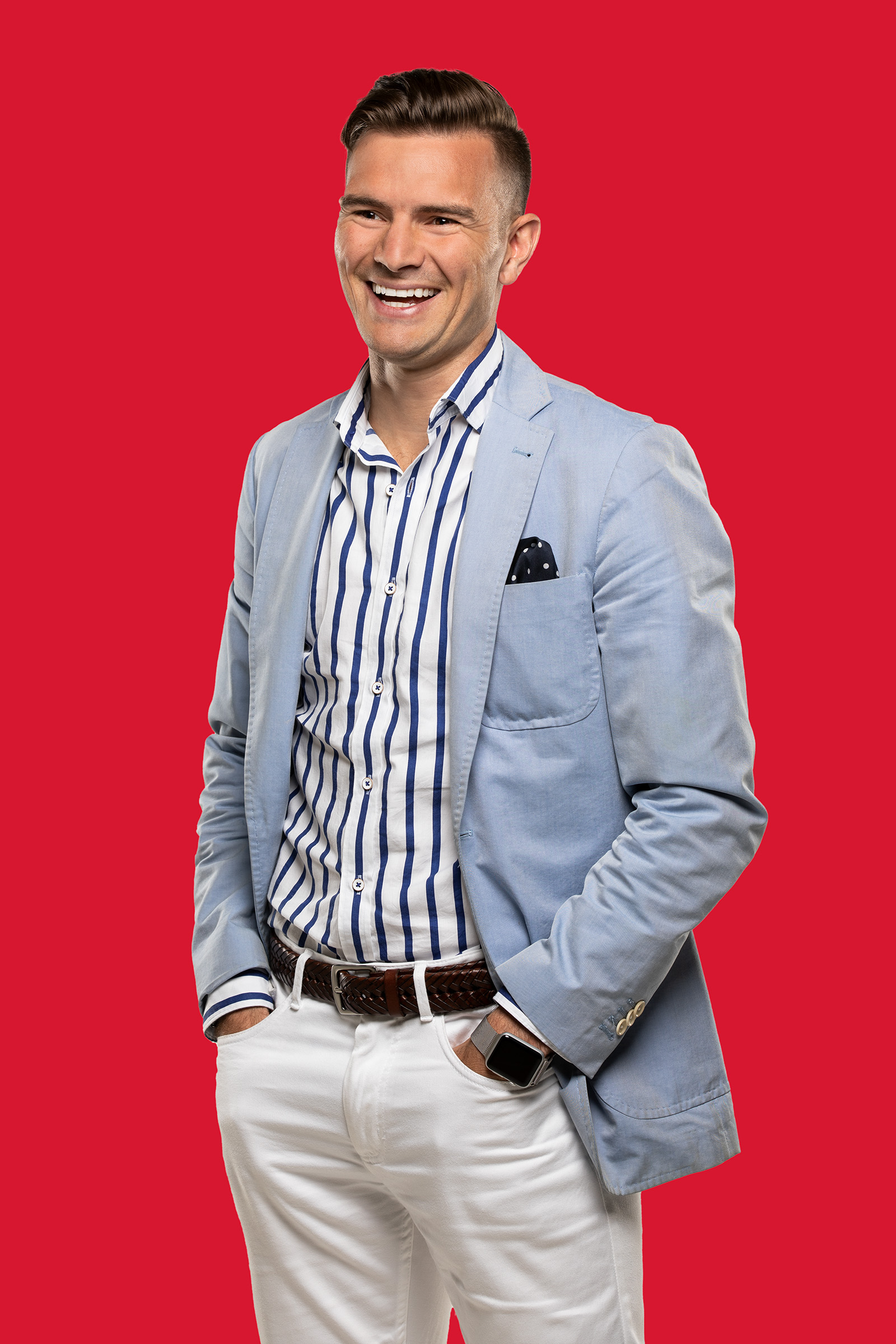 man standing with hands in pockets on red background