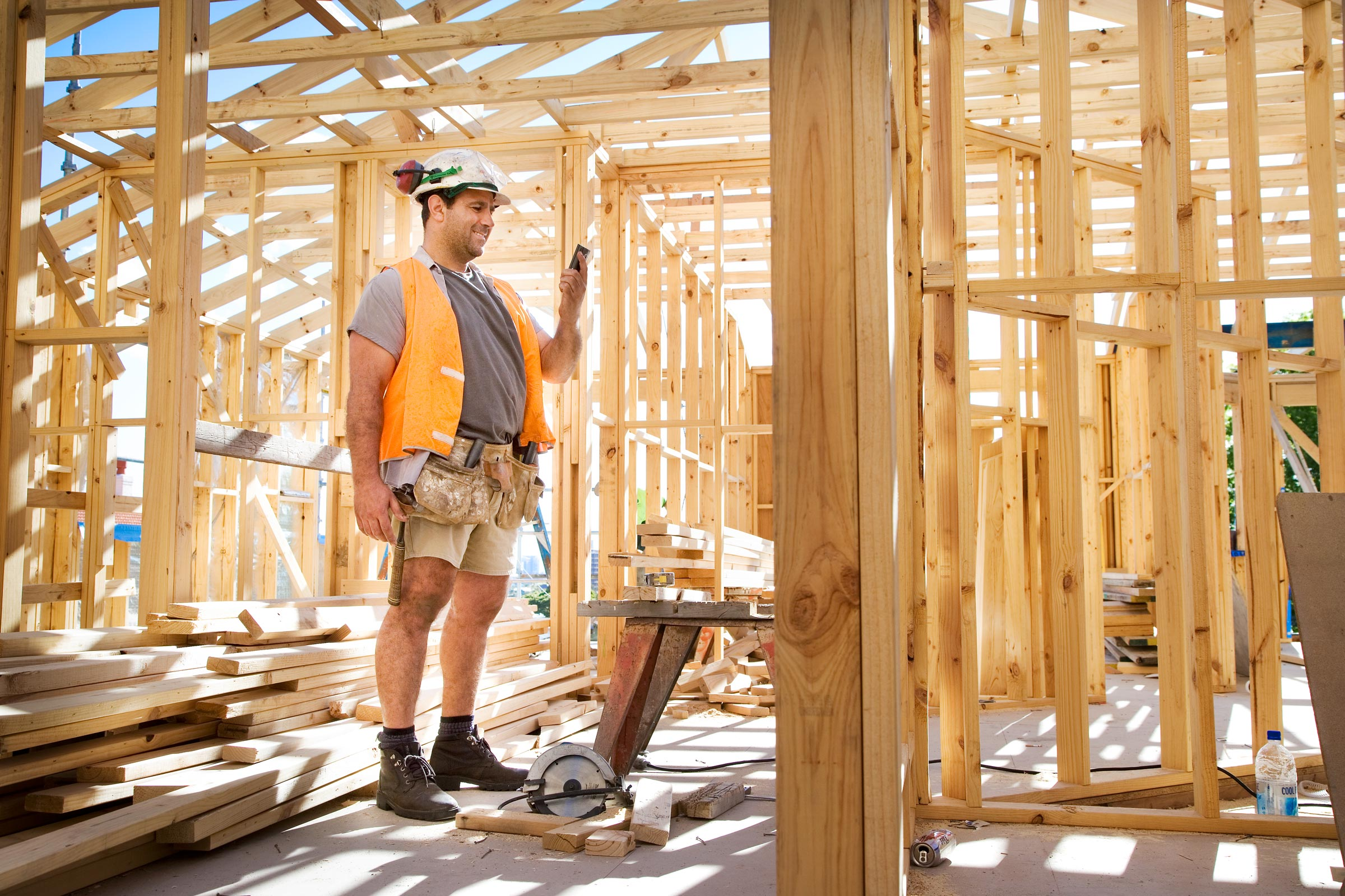construction worker using phone in house build