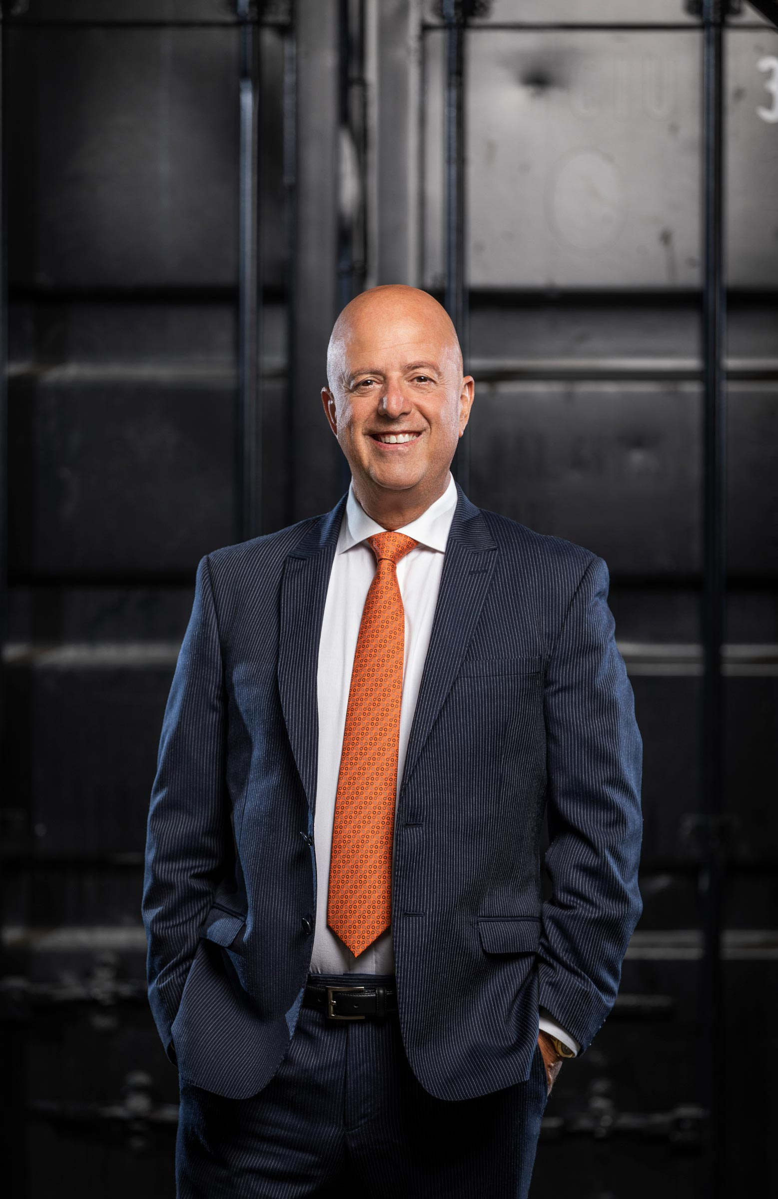 corporate male in suit with orange tie standing in front of shipping container