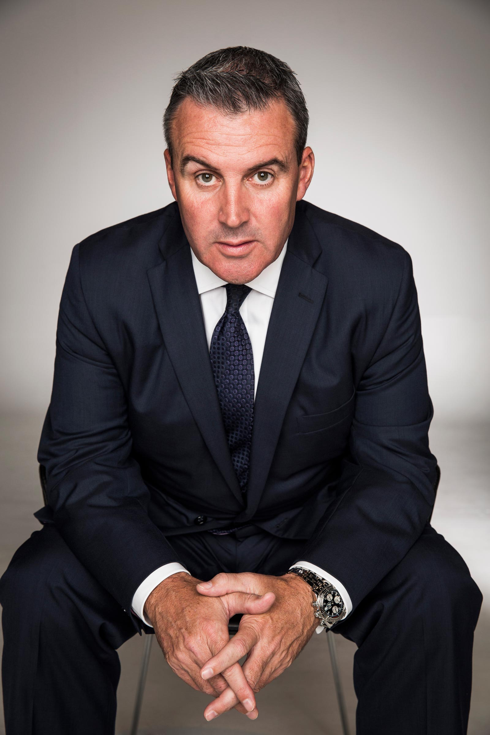 Male corporate portrait sitting on chair in blue suit