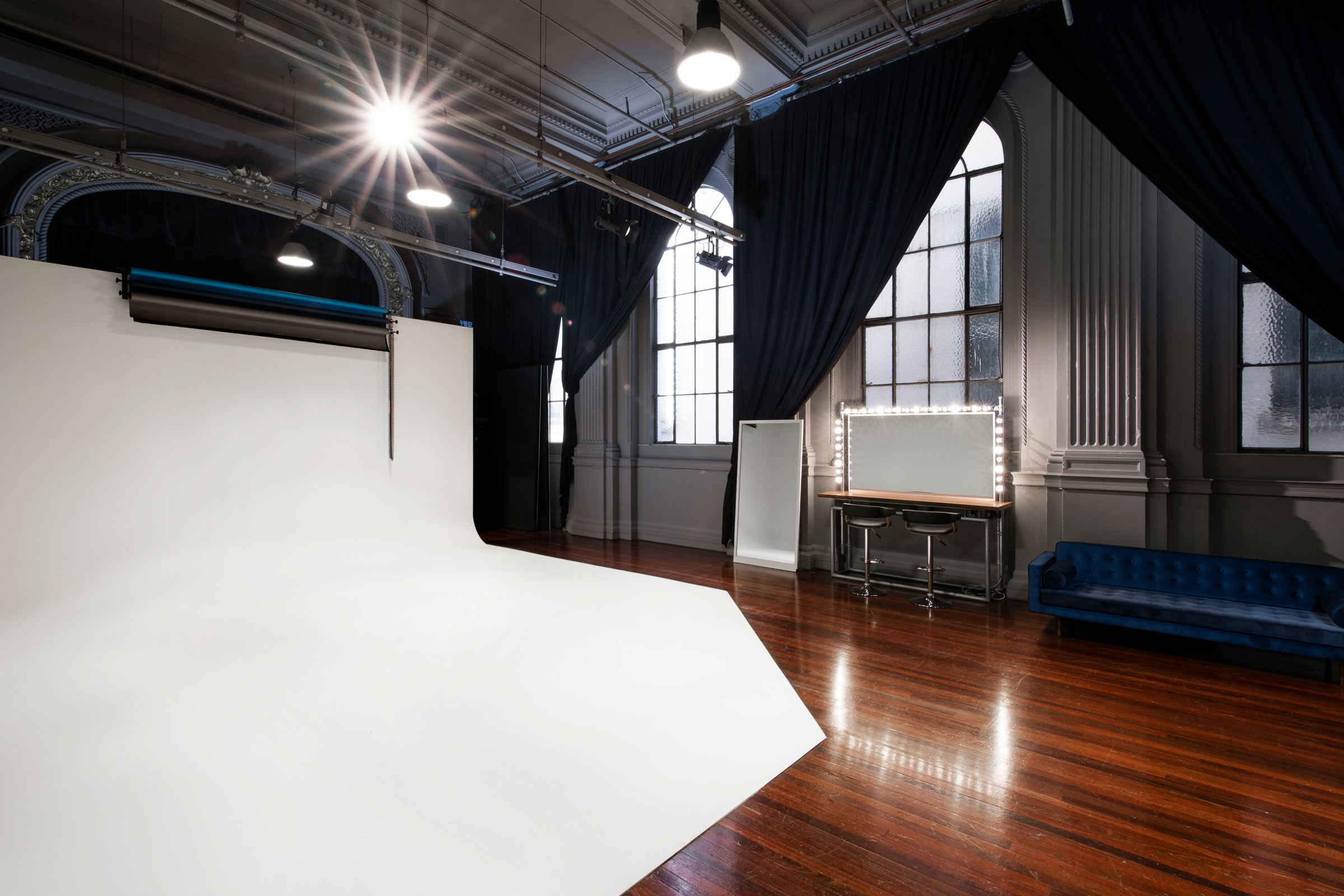 white cyclorama with a makeup mirror and blue couch